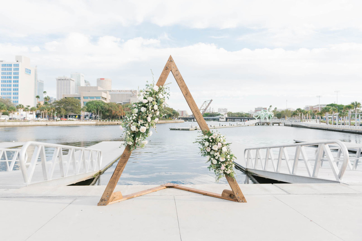 Boho Chic Waterfront Wedding Ceremony Decor, Triangular Wooden Arch with Lush Greenery and White, Ivory Roses | Wedding Venue The Tampa River Center | Wedding Venue Parties A'la Carte | Wedding Florist Bruce Wayne Florals
