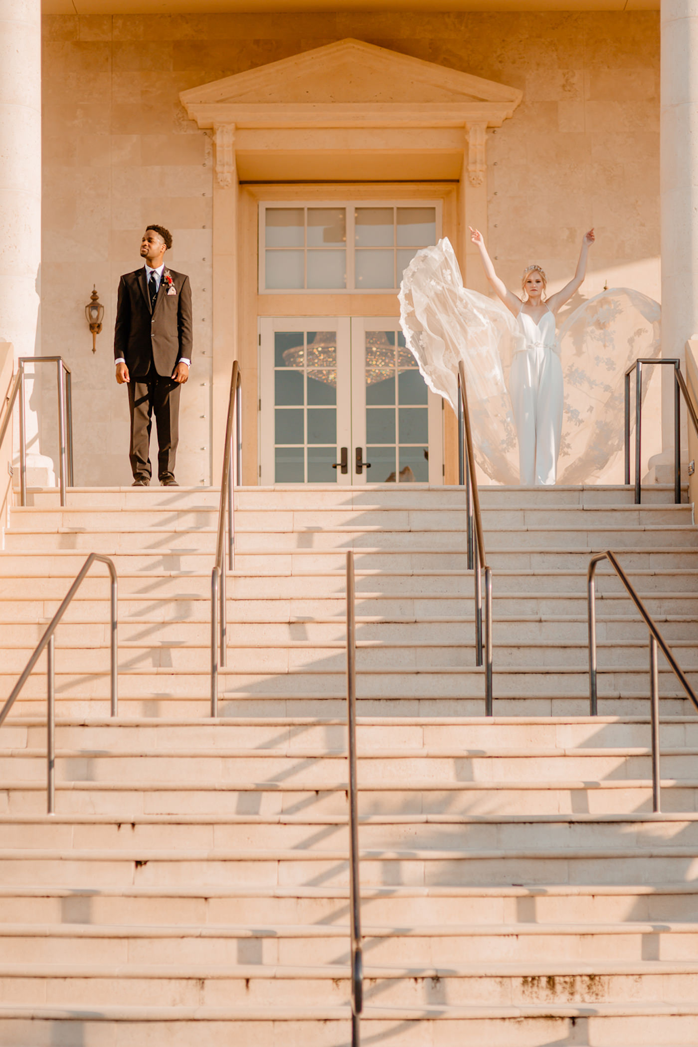 Bride and Groom Outdoor Wedding Portrait on Grand Staircase | Embroidered Floral Lace V Neck Bridal Gown and Groom in Classic Black Tux