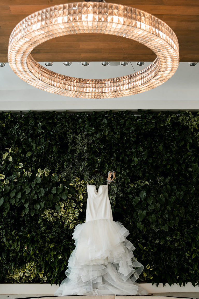 Elegant Wedding Dress Hanging Outside Greenery Wall at Florida Wedding Venue Hilton Clearwater Beach