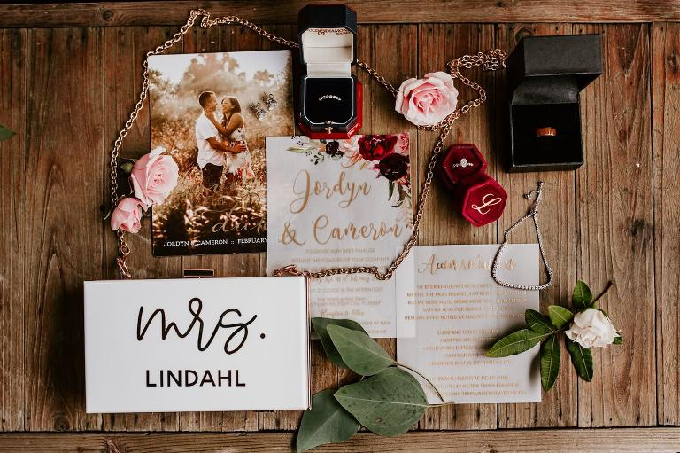 Tampa Wedding Stationery Suite Flat Lay Photo | Maroon Burgundy Deep Red Blush Pink Floral Vellum with Gold Calligraphy and Red Velvet Ring Box | Custom Name Bride Purse Clutch
