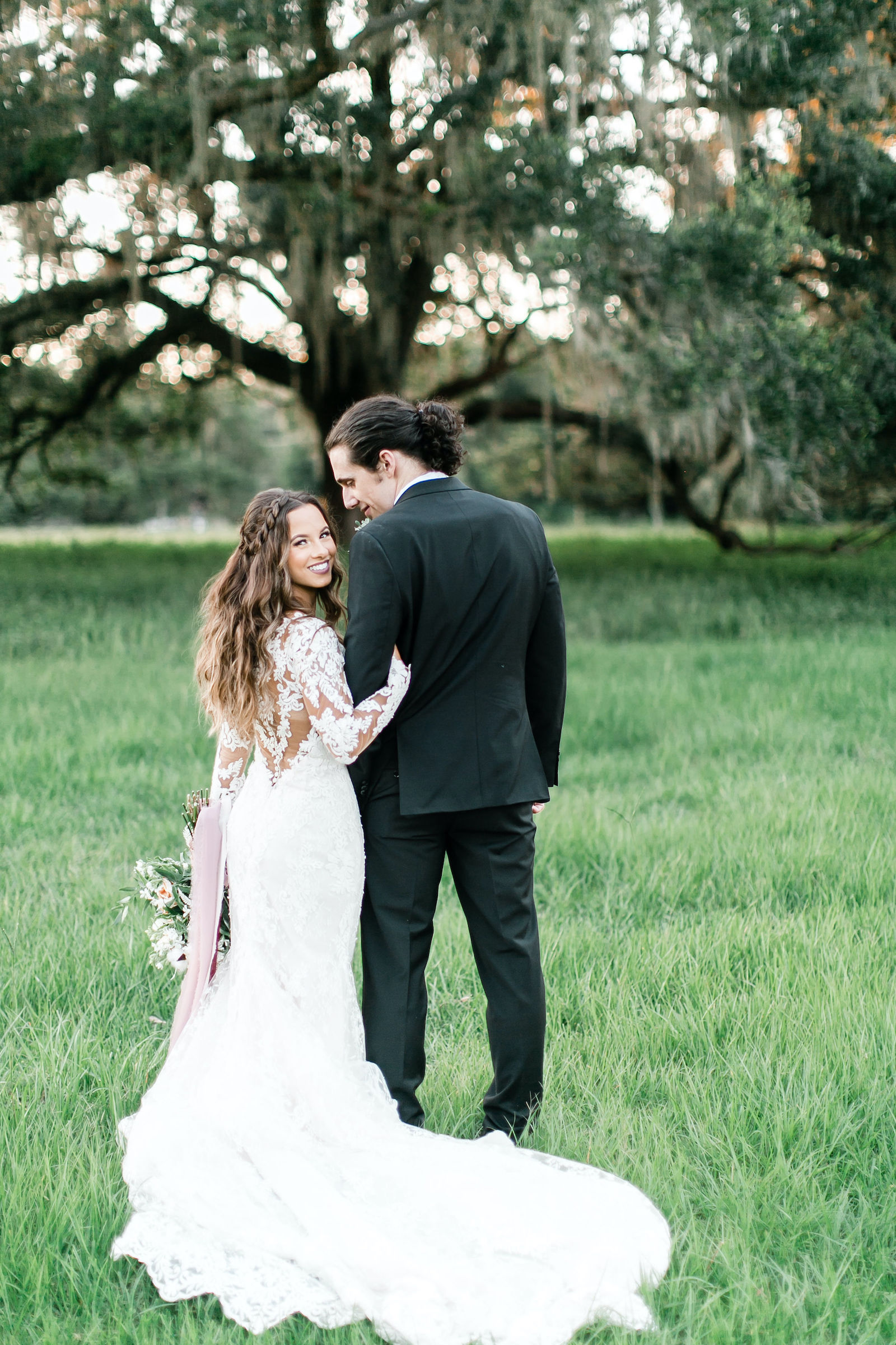 Lace Mermaid Long Sleeve Low Back Illusion Lace Bridal Gown Wedding Dress | Groom in Classic Black Suit Tux