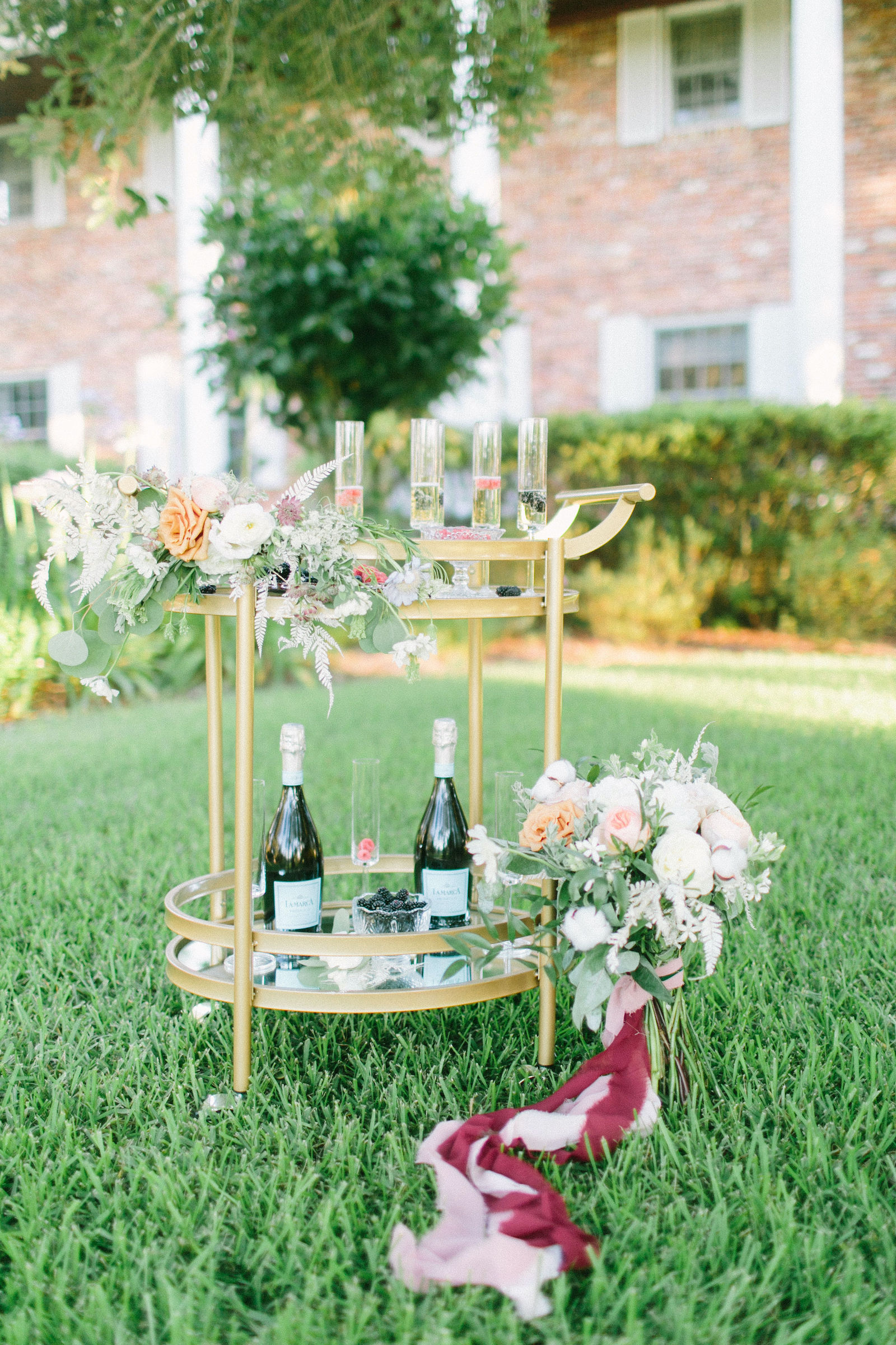 Outdoor Brunch Breakfast Wedding Champagne Cart Bubbly Bar with Gold Vintage Bar Cart and Fresh Berries | Ivory Champagne and Peach Natural Bouquet with Roses Astilbe and Greenery tied with Blush Pink and Mauve Ribbons