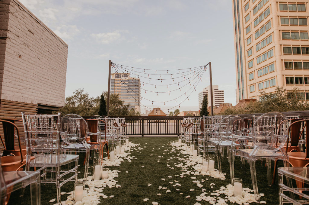 Modern Rooftop Wedding Ceremony with City Skyline and Mismatched Clear Acrylic Chairs and Industrial Copper Chairs | Unique, Historic Downtown St. Pete Wedding Venue Station House | St. Petersburg Wedding Planner Blue Skies Events