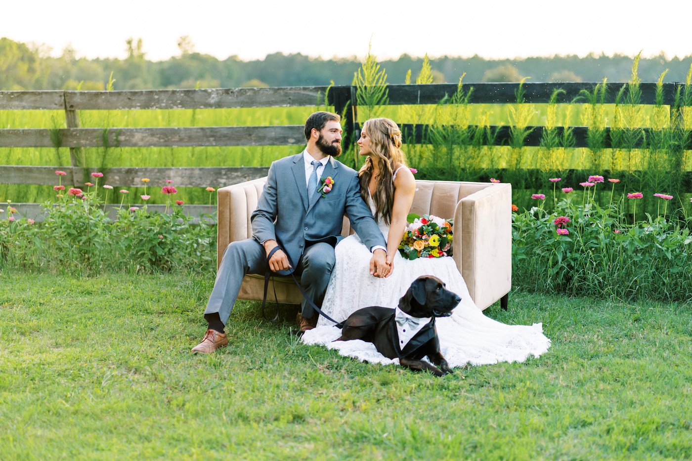 Bright Colorful Florida Citrus Wedding Inspiration | Bridal Bouquet with Pink Orange and Yellow Roses | Groom in Grey Suit with Grey Neck Tie | Wedding Dog of Honor with Bow Tie Collar | Outdoor Bride and Groom Portrait with Love Seat