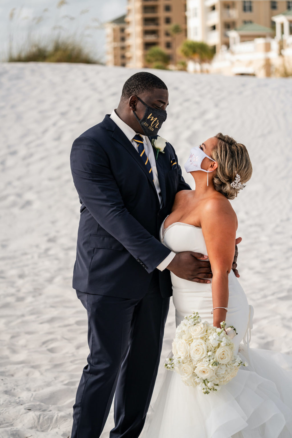 Destination Wedding During Pandemic. COVID Bride and Groom Beachfront Wedding Portraits Wearing Mr. and Mrs. Masks, Romantic Tropical Bride and Groom Just Married on the sand of Clearwater Beach, Bride Wearing Sophisticated Fit and Flare Strapless Wedding Dress | Florida Gulf of Mexico Hotel and Wedding Venue Hilton Clearwater Beach