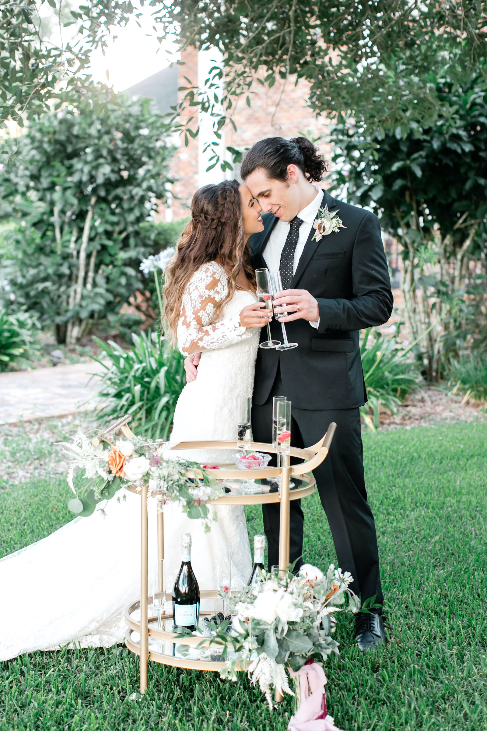Outdoor Brunch Breakfast Wedding Champagne Cart Bubbly Bar with Gold Vintage Bar Cart and Fresh Berries | Lace Mermaid Long Sleeve Bridal Gown Wedding Dress | Groom in Classic Black Suit Tux