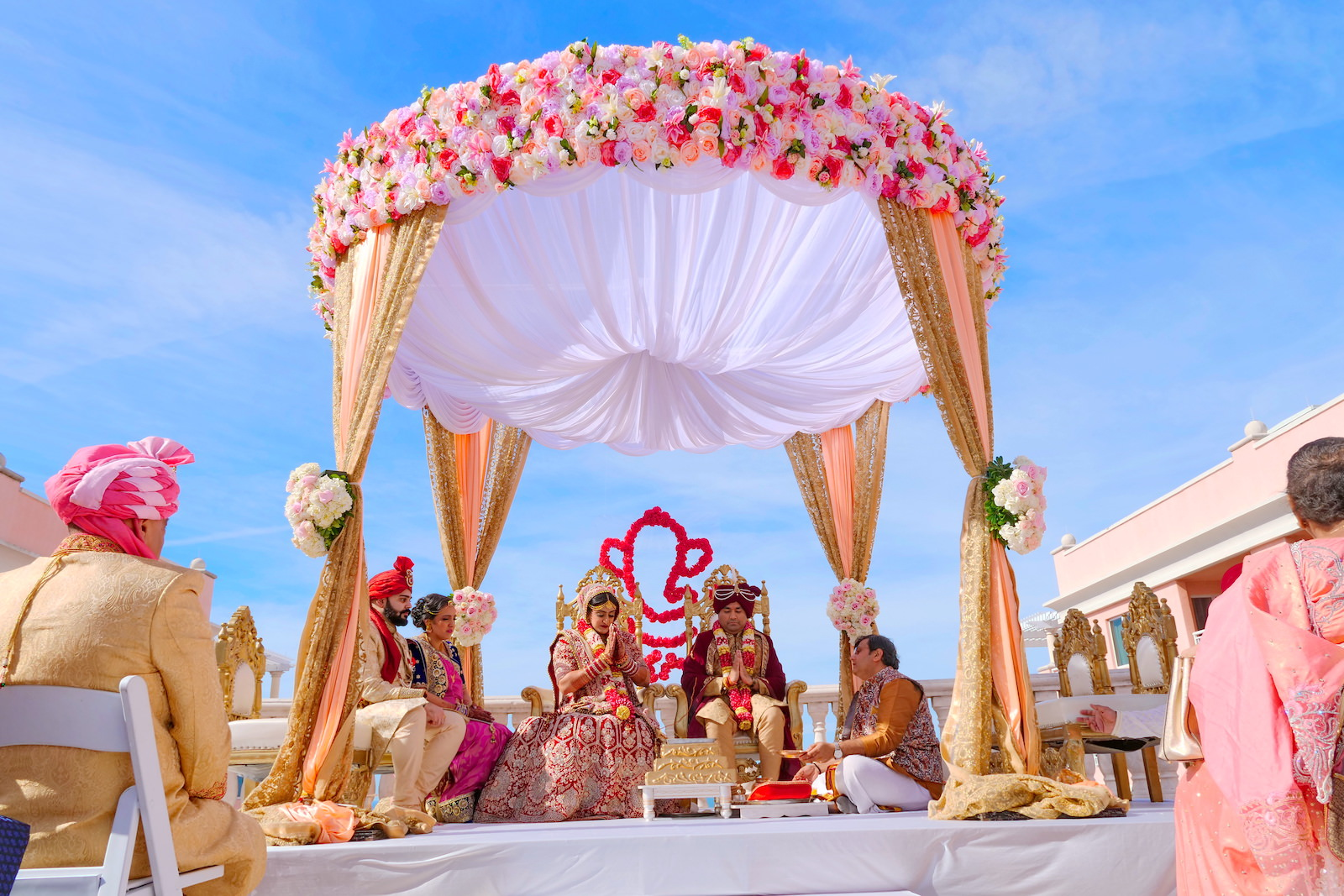 Rooftop Indian Wedding Ceremony at Clearwater Wedding Venue Hyatt Regency Clearwater Beach | Pink and Gold Mandap with Draping and Roses and Floral Elephant