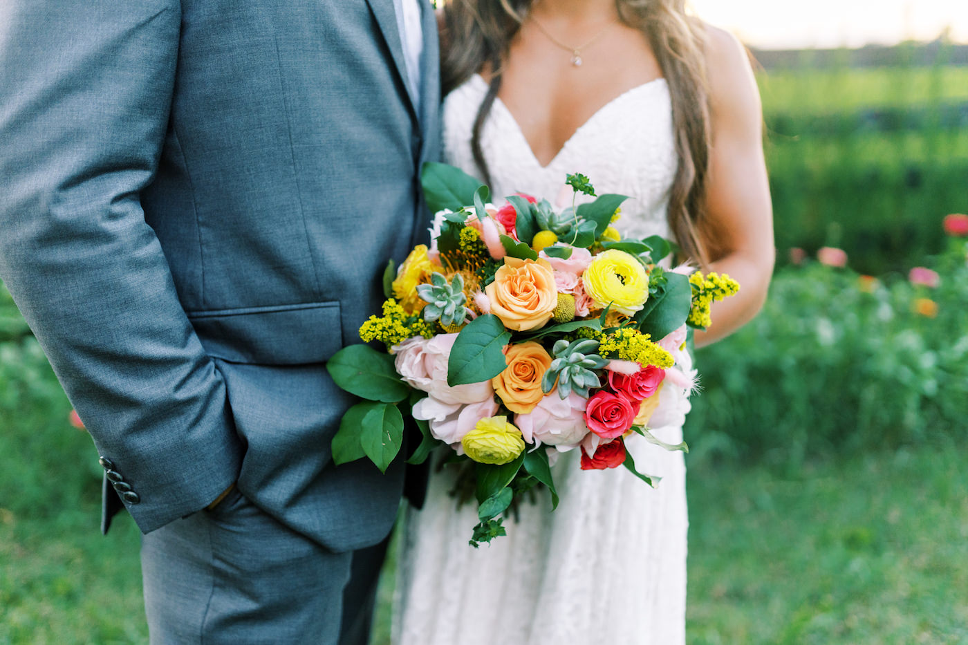 Bright Colorful Florida Citrus Wedding Inspiration | Bridal Bouquet with Pink and Orange Roses Yellow Ranunculus and Succulents | Groom in Grey Suit