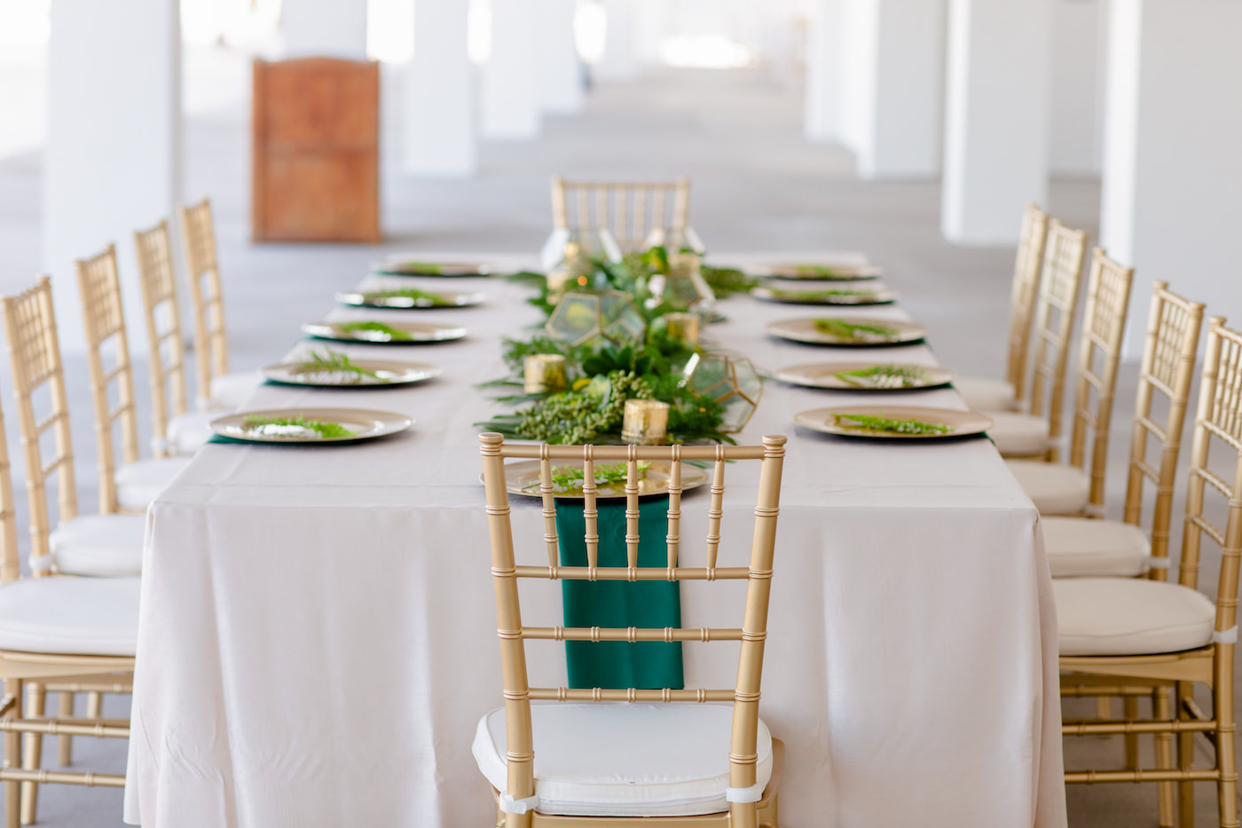 Clearwater Beach Wedding Venue Hilton Clearwater Beach   Modern Tropical Beach Outdoor Wedding Reception Terrace Feasting Table with Champagne Table Linens and Emerald Green Napkins under Gold Charger Plates   Gold Chiavari Chairs and Tropical Palm Frond Leaf Floral Arrangement Garland