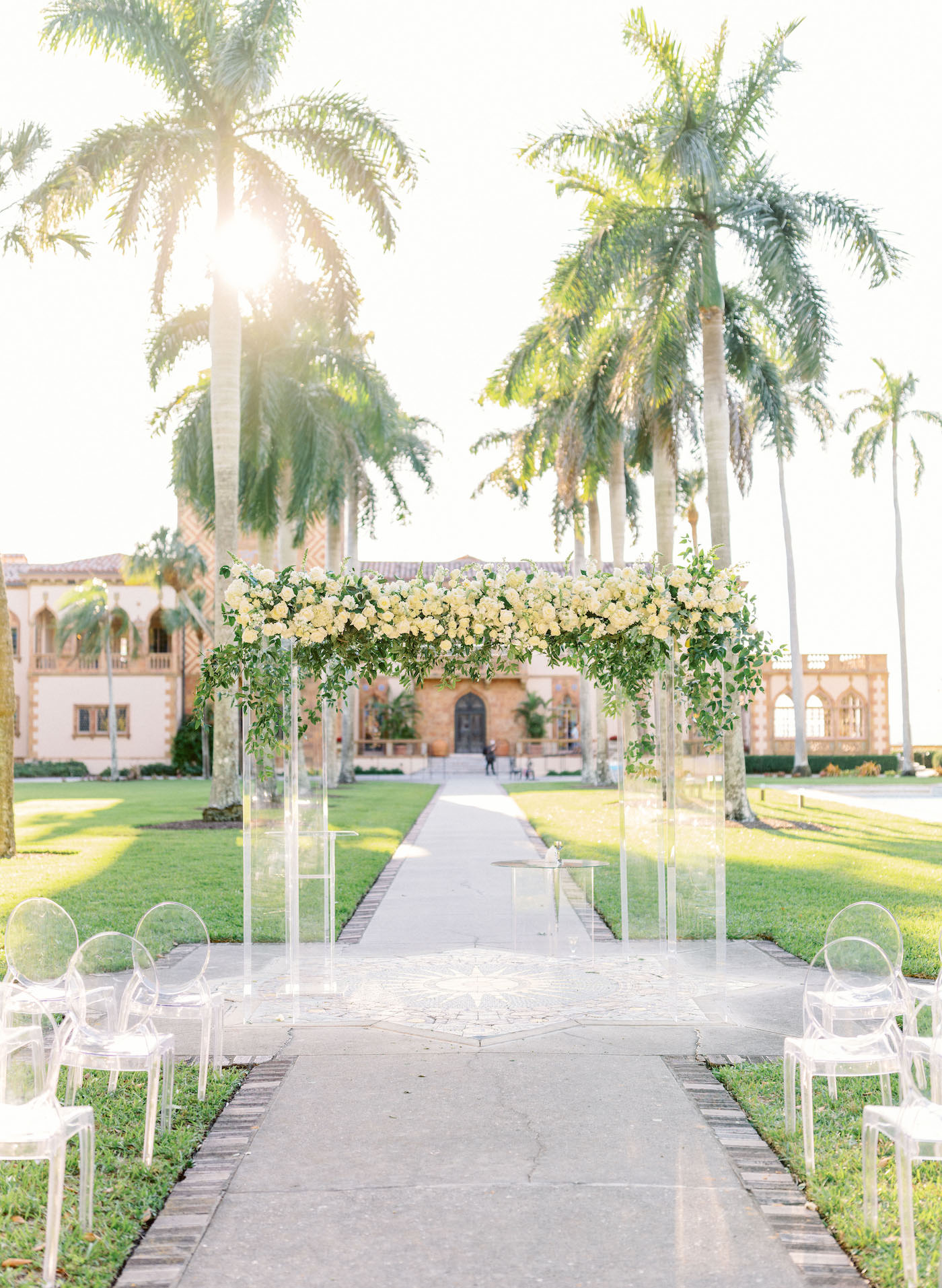 Romantic, Modern Florida Outdoor Wedding Ceremony with Jewish Wedding Altar, Ghost Chairs, Clear Acrylic Chuppah with Lush Ivory Floral Bouquets and Greenery, In Courtyard of The Ringling Museum | Sarasota Wedding Planner NK Weddings