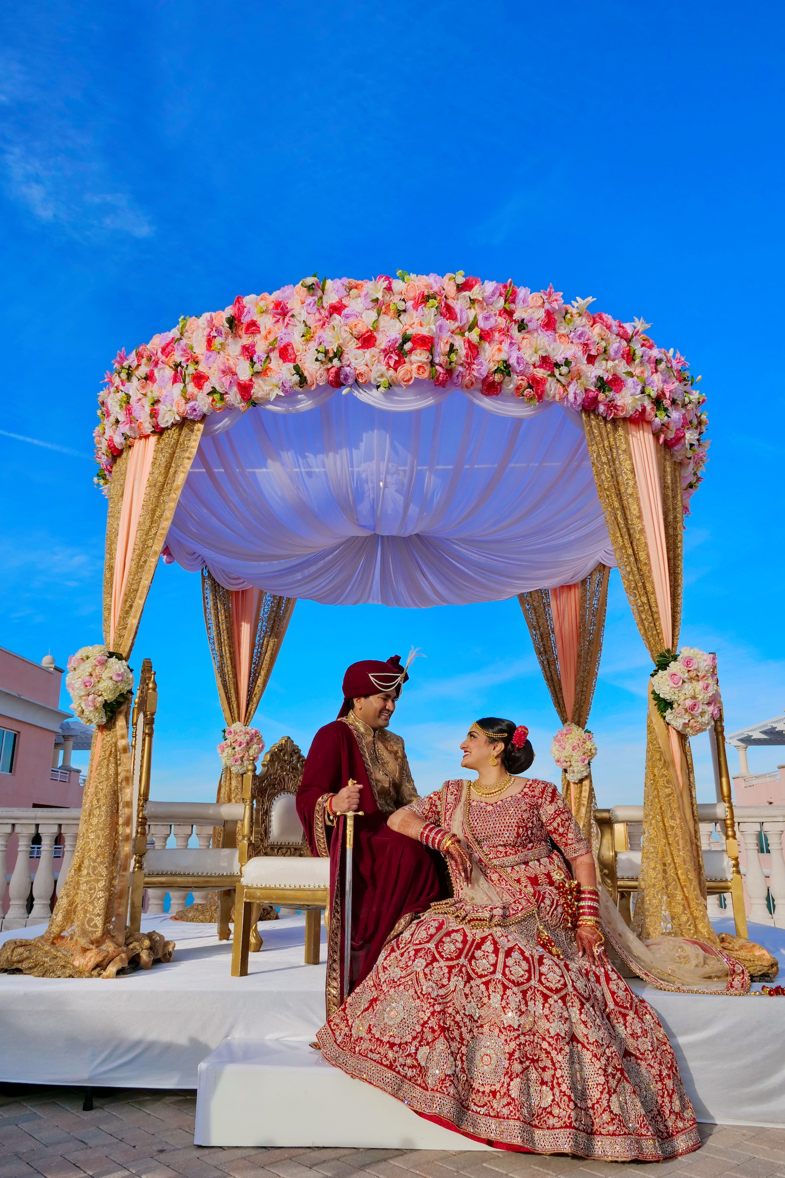 Bride and Groom Outdoor Portrait | Traditional Red and Gold Indian Wedding Dress Lehenga Saree | Rooftop Indian Wedding Ceremony at Clearwater Wedding Venue Hyatt Regency Clearwater Beach | Pink and Gold Mandap with Draping