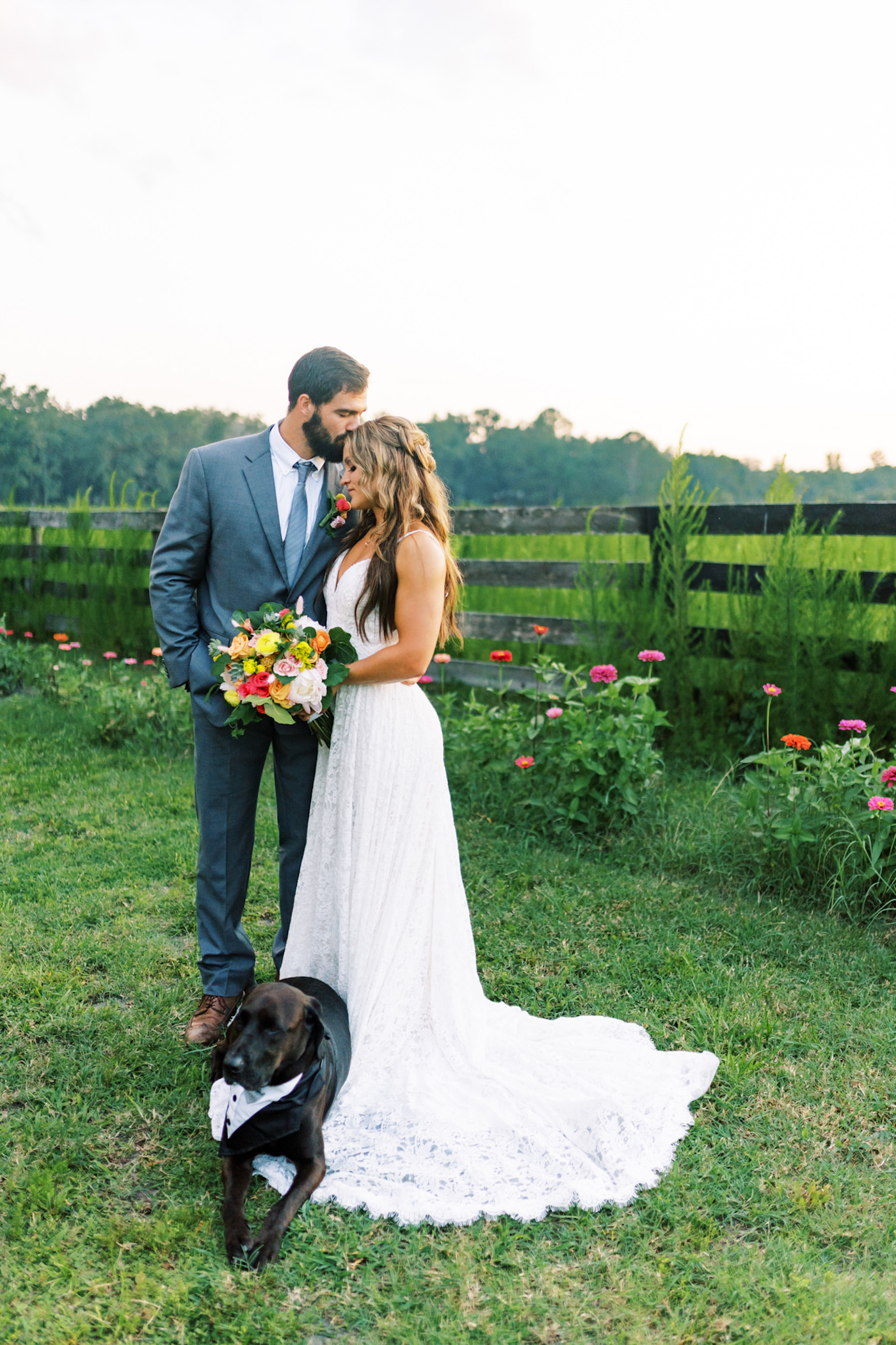 Bright Colorful Florida Citrus Wedding Inspiration | Bridal Bouquet with Pink Orange and Yellow Roses | Groom in Grey Suit with Grey Neck Tie | Wedding Dog of Honor with Bow Tie Collar | Outdoor Bride and Groom Portrait