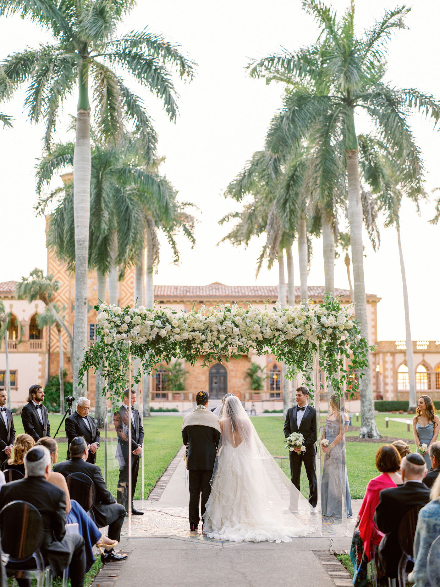 Romantic, Modern Florida Bride and Groom During Outdoor Wedding Ceremony with Jewish Altar, Ghost Chairs, Clear Acrylic Chuppah with Lush Ivory Floral Bouquets and Greenery Decor, In Courtyard of The Ringling Museum | Sarasota Wedding Planner NK Weddings