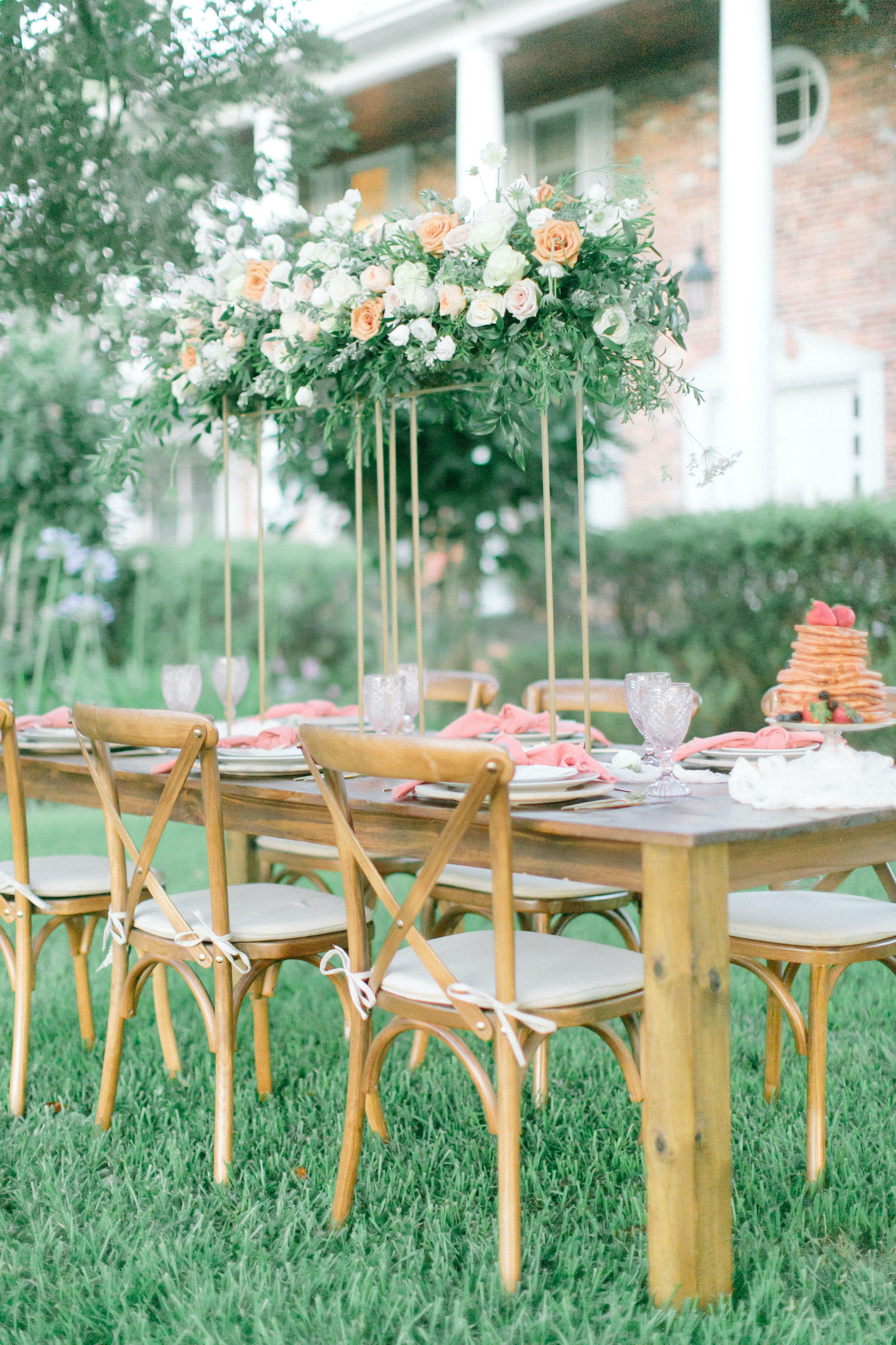 Outdoor Styled Shoot Brunch Breakfast Wedding Reception Wood Farm Table with French Country Cross Back Chairs and Place Setting with Gold Flatware and Whitewash Wood Charger Plate | Natural White Champagne and Peach Tall Centerpiece with Roses Queen Anne Lace and Greenery on Gold Geometric Stand | Blush Pink Napkins and Vintage Glassware Goblets at Place Settings | Crepe Pancake Wedding Cake