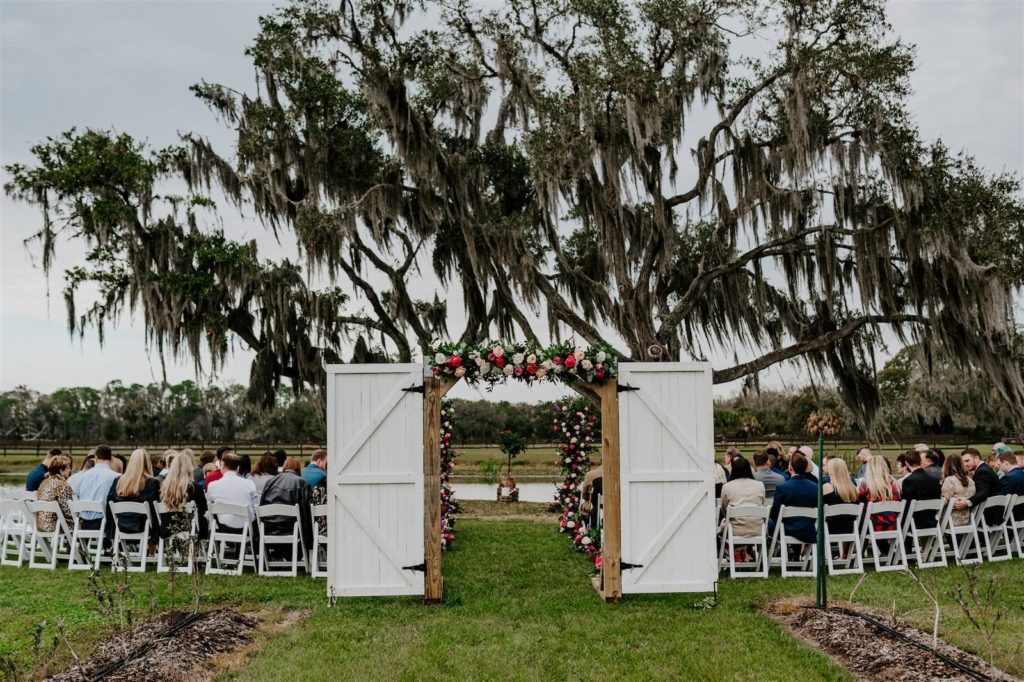 Rustic Tampa Outdoor Oak Tree Wedding Ceremony with White Garden Chairs | Wedding Barn Doors Entrance with Floral Garland | Tampa Wedding Florist Monarch Events and Designs | Deep Red Maroon Burgundy Roses and Blush Pink and White Roses with Eucalyptus Greenery