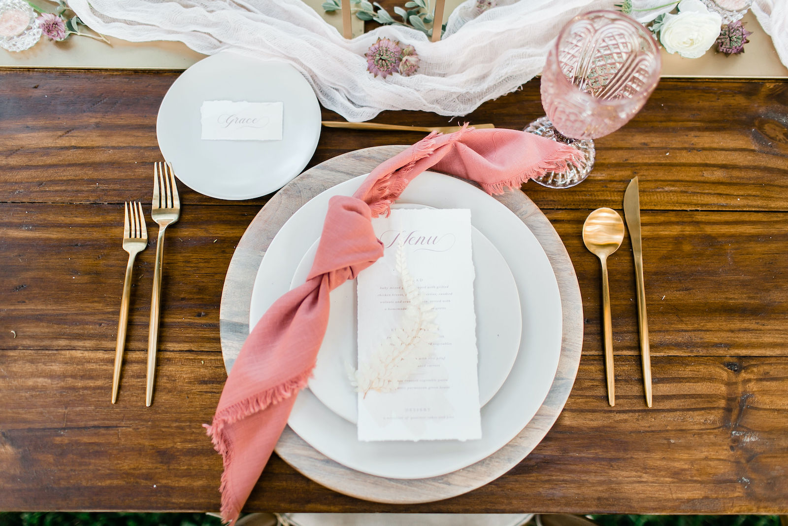 Outdoor Styled Shoot Brunch Breakfast Wedding Reception Table Place Setting with Gold Flatware and Whitewash Wood Charger Plate with Blush Pink Napkins and Menu Card and Vintage Glassware Goblets at Place Settings