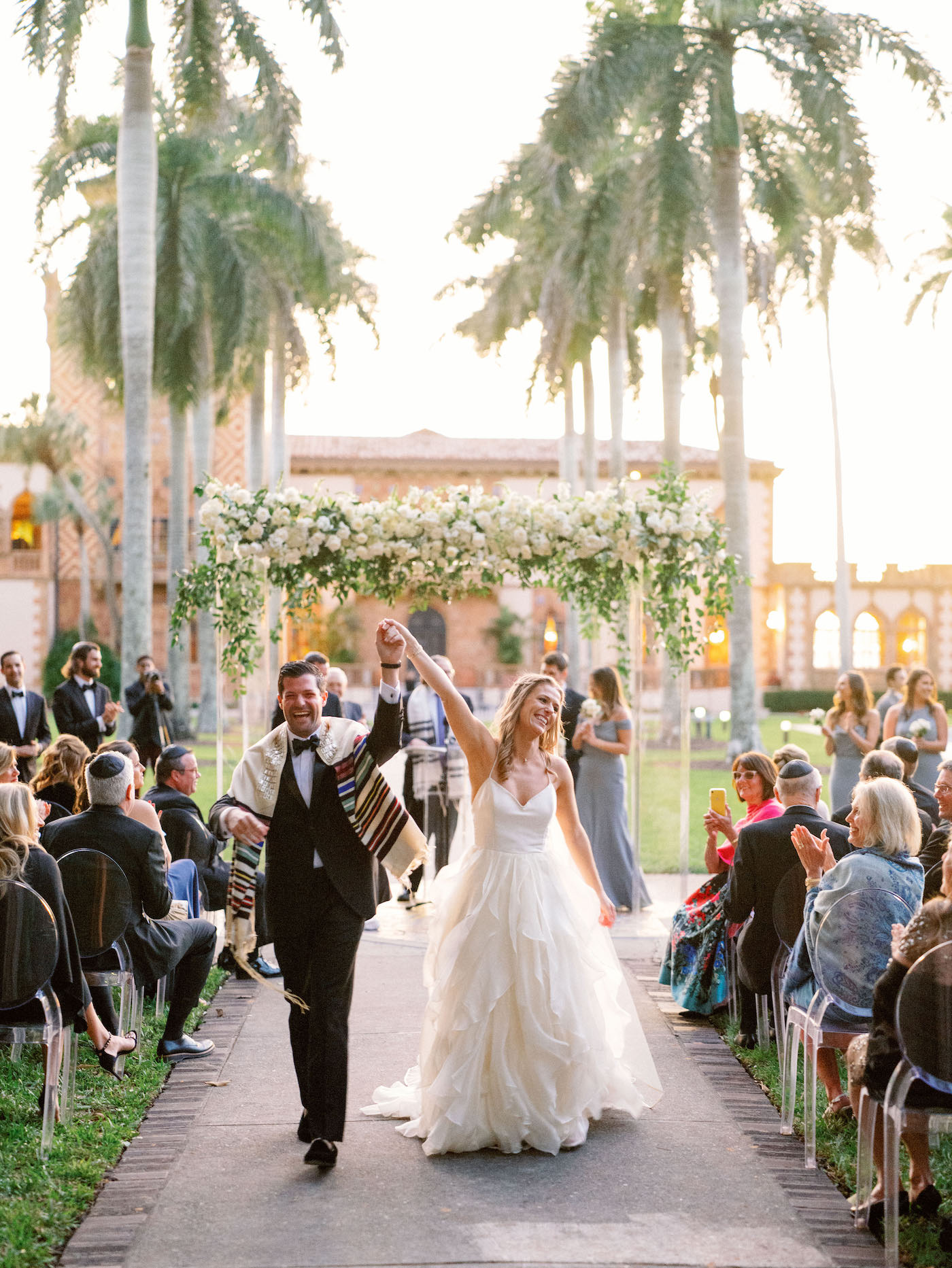 Romantic, Modern Florida Bride and Groom Just Married Recessional, Outdoor Wedding Ceremony with Jewish Altar, Ghost Chairs, Clear Acrylic Chuppah with Lush Ivory Floral Bouquets and Greenery Decor, In Courtyard of The Ringling Museum | Sarasota Wedding Planner NK Weddings