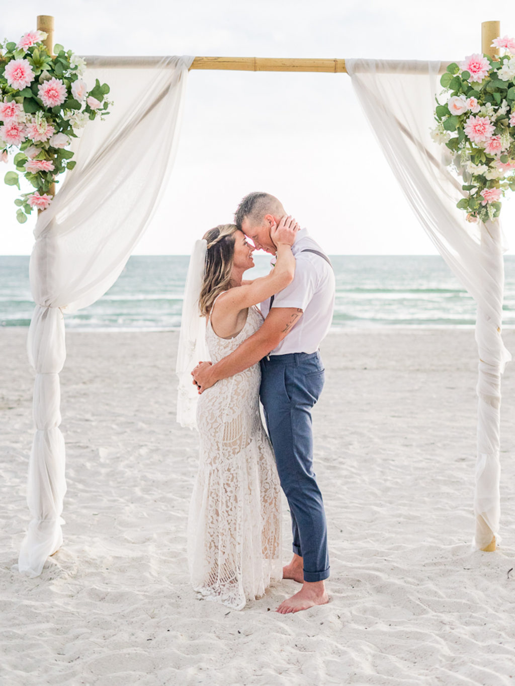 St. Petersburg Florida Beach Wedding Ceremony | Bamboo Arch Backdrop with Sheer White Draping and Blush Pink Floral Arrangements | Outdoor Bride and Groom Portrait | Groom Navy Blue Pants with White Short Sleeve Shirt and Suspenders and Flip Flops | Lace Sheath Spaghetti Strap V Neck Boho Bridal Gown Wedding Dress