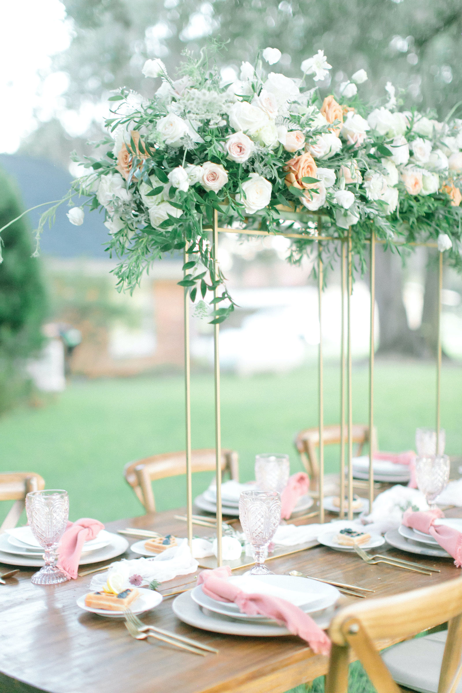 Outdoor Styled Shoot Brunch Breakfast Wedding Reception Table Place Setting with Gold Flatware and Whitewash Wood Charger Plate | Natural White Champagne and Peach Tall Centerpiece with Roses Queen Anne Lace and Greenery on Gold Geometric Stand | Blush Pink Napkins and Vintage Glassware Goblets at Place Settings