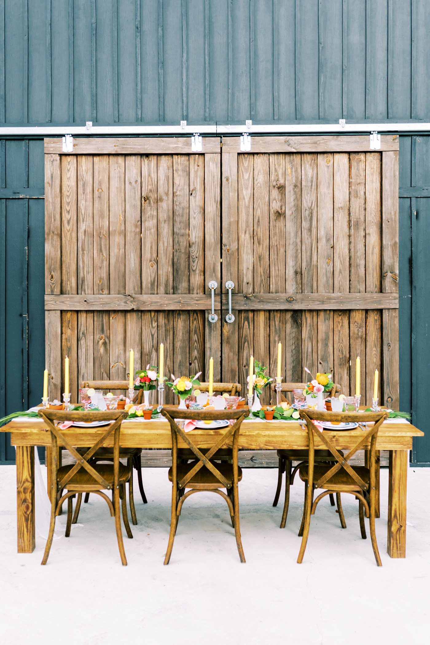 Bright Colorful Florida Citrus Wedding Inspiration | Outdoor Reception Table at Rustic Barn Farm Venue | Wood Farm Feasting Table with Wood French Country Cross Back Chairs | Wedding Centerpiece with Colorful Bud Vases and Taper Candles