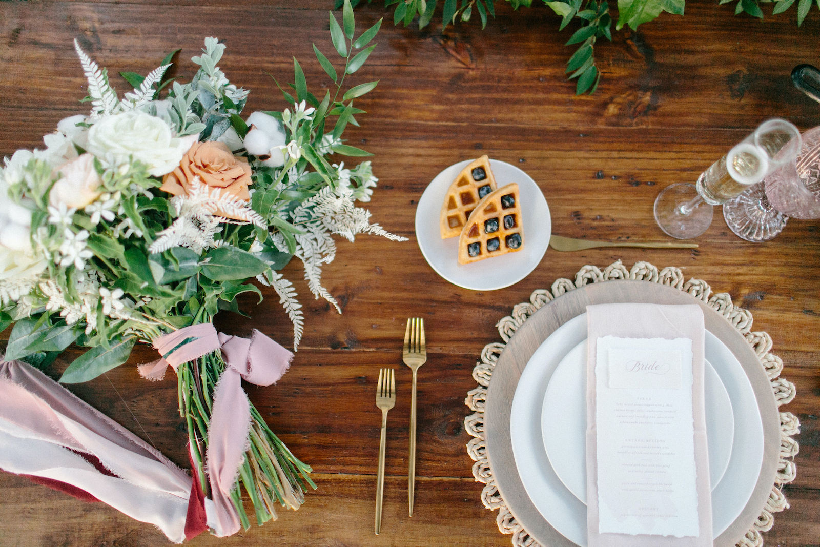 Styled Shoot Brunch Breakfast Wedding Place Setting with Gold Flatware, Menu Card on Blush Napkin, Whitewash Wood Charger Plate and Woven Rattan Rope Placemat | Natural White and Peach Bouquet with Roses Astilbe Cotton and Greenery tied with Blush Pink Ribbon