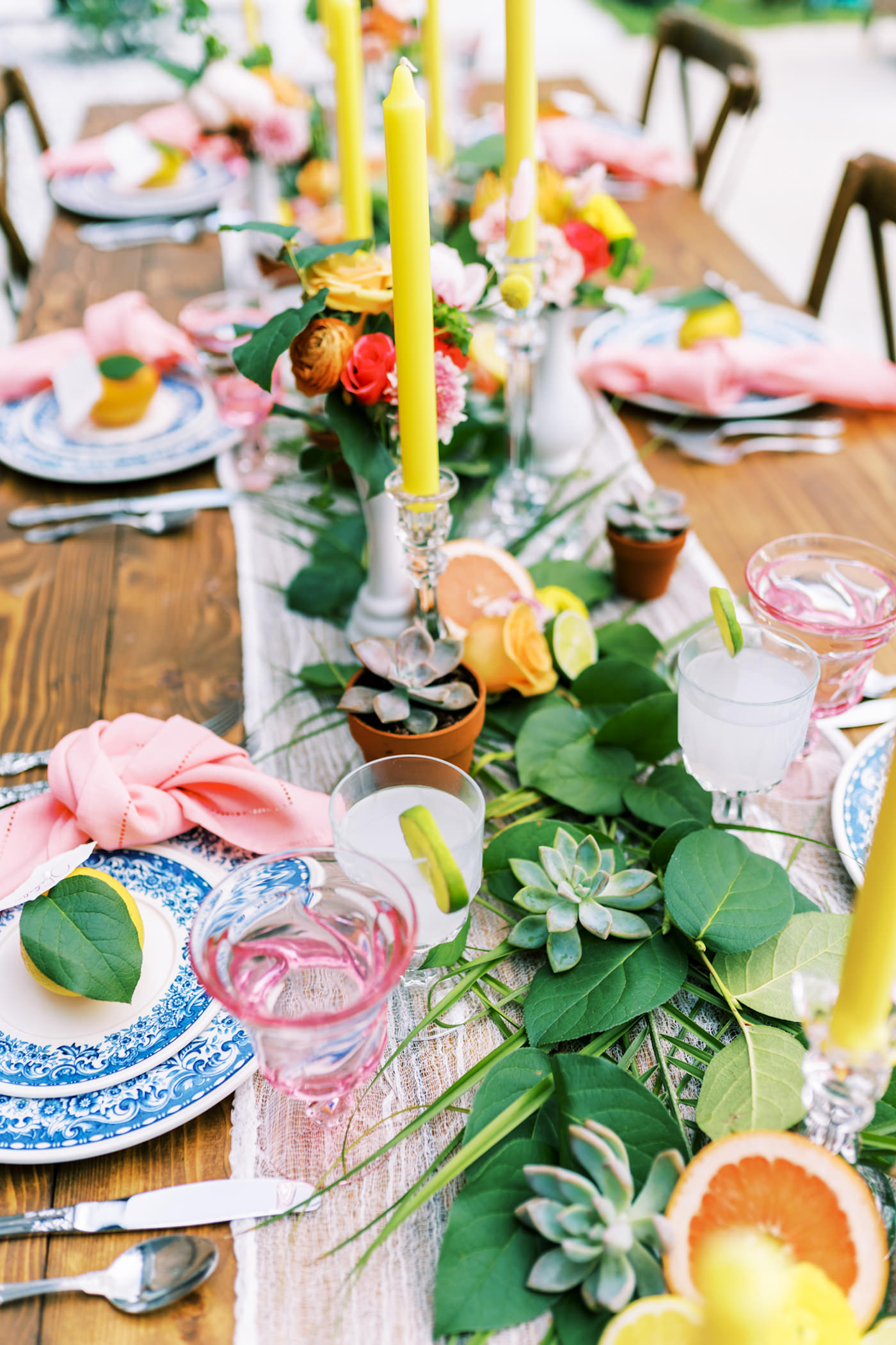 Bright Colorful Florida Citrus Wedding Inspiration | Outdoor Reception Wood Farm Feasting Table Wedding Centerpiece with Greenery Garland with Oranges and Succulents and Colorful Taper Candles | Wedding Place Settings with Vintage Blue China and Pink Glass Goblets and Pink Napkins
