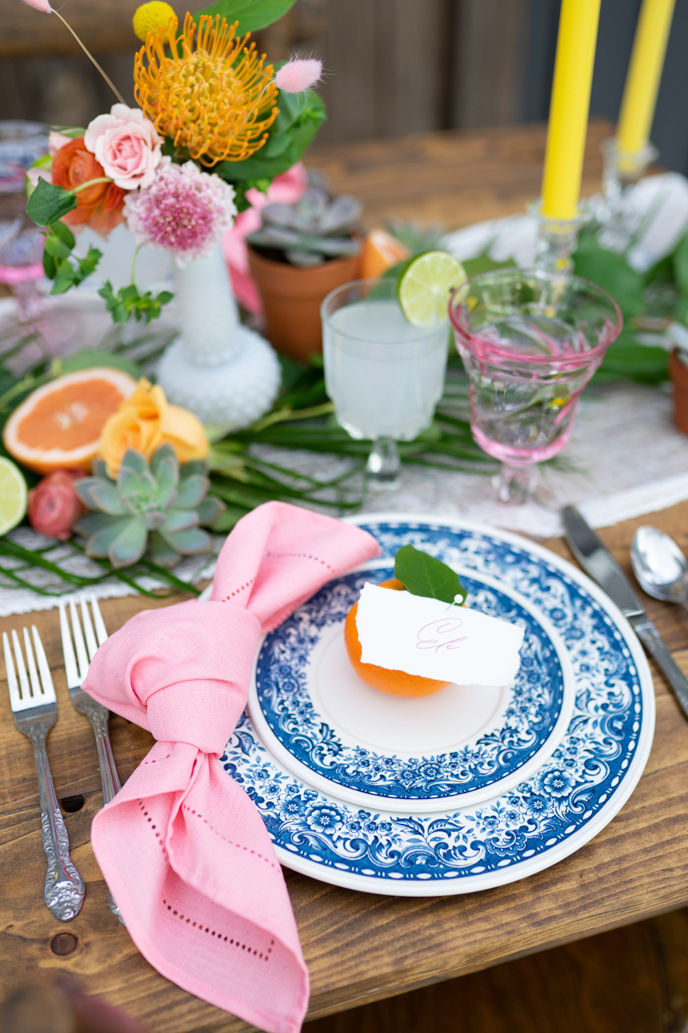 Bright Colorful Florida Citrus Wedding Inspiration | Outdoor Reception Wood Farm Feasting Table Wedding Centerpiece with Greenery Garland with Oranges and Succulents and Colorful Taper Candles | Wedding Place Settings with Vintage Blue China and Pink Glass Goblets and Pink Napkins and Citrus Orange Place Cards