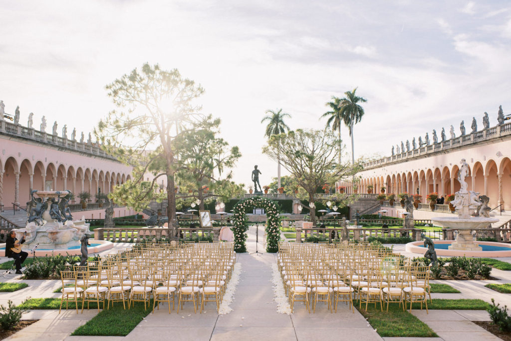 Fairytale Inspired Florida Wedding Ceremony at The Ringling Museum of Art Courtyard in Sarasota, Gold Chiavari Chairs, White Ivory Rose Petals as Aisle Liner, Large Floral Arch with White and Blush Pink Roses | Florida Wedding Planner NK Weddings