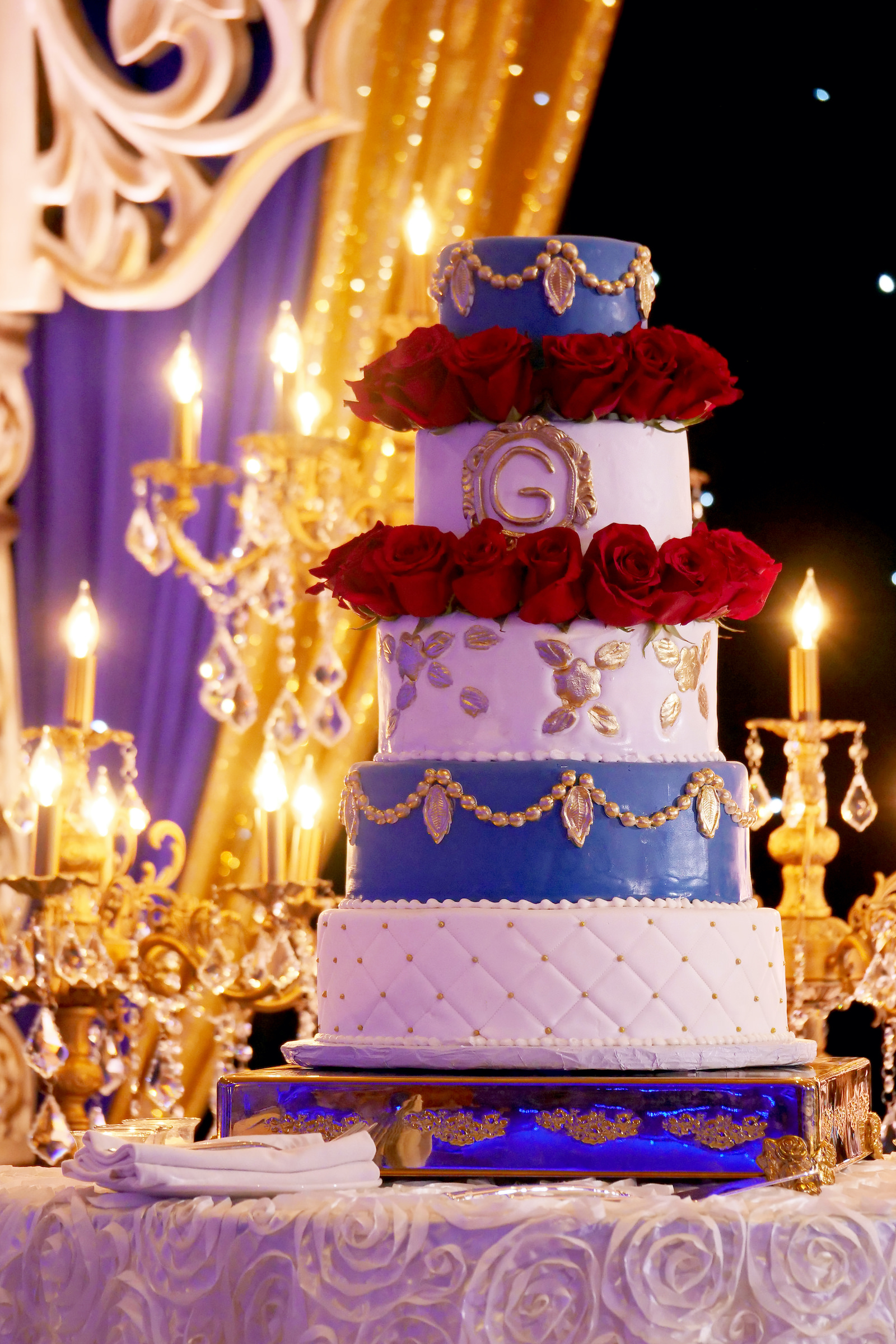 Five Tier Fondant Indian Wedding Cake with Gold Monogram and Quilting accented with Red Roses on a Gold Cake Stand