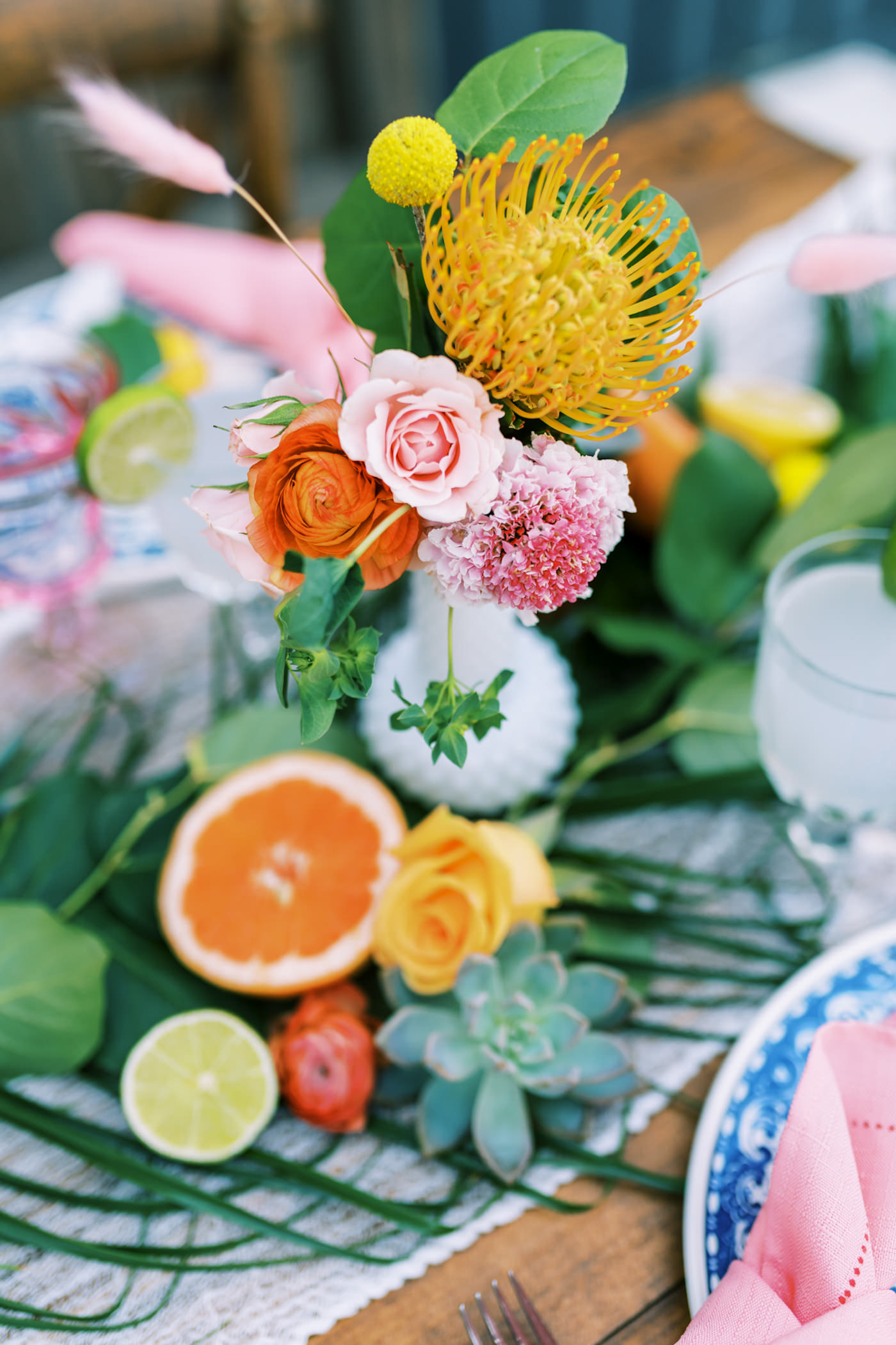 Bright Colorful Florida Citrus Wedding Inspiration | Outdoor Reception Wood Farm Feasting Table Wedding Centerpiece with Greenery Garland with Oranges and Succulents and Colorful Bud Vases with Pink Scabiosa Orange Roses and Yellow Pincushion Protea