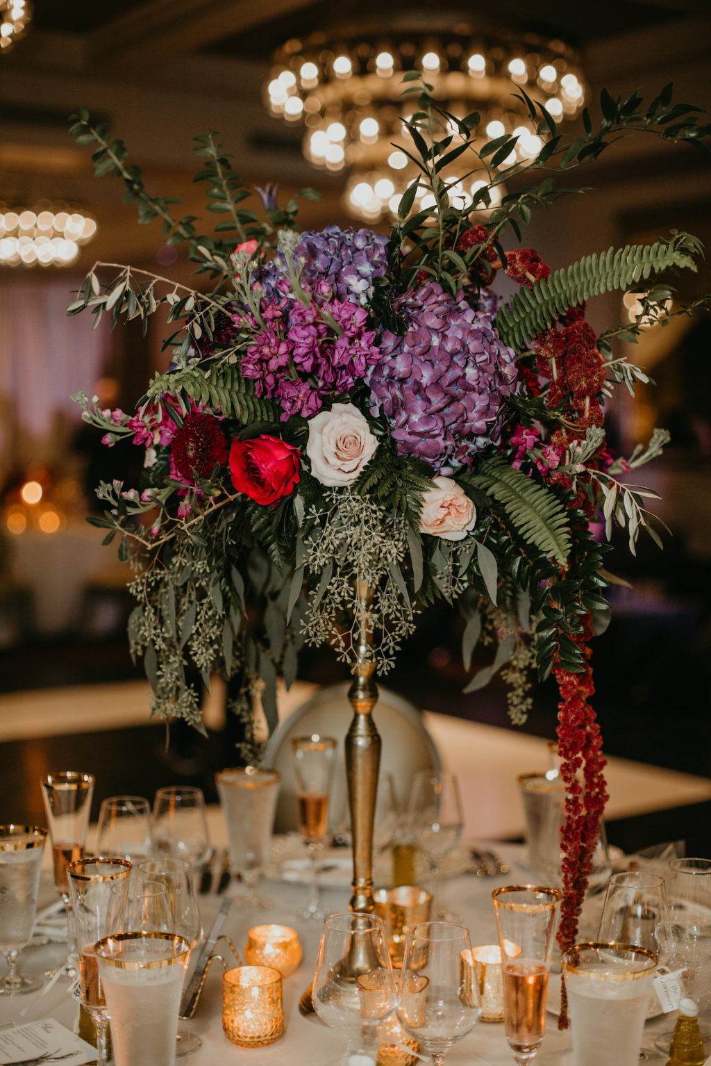 Wedding Centerpiece Inspiration | Tall Candlestick Centerpiece with Loose Cascading Floral Arrangement of Purple Hydrangea, Deep Red Burgundy Roses and Amaranthus, Olive Branches and Eucalyptus Greenery