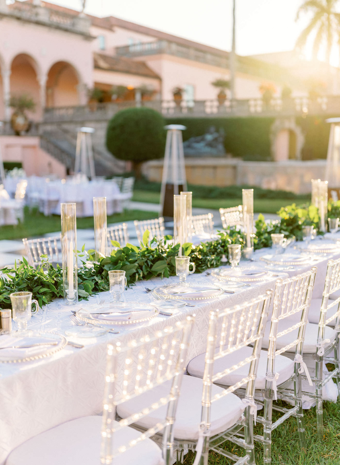 Romantic, Modern Outdoor Florida Wedding Reception, Wedding Party Long Feasting Table with White Linens and Clear Acrylic Chiavari Chairs, Greenery Garland Centerpiece with Tall Taper Candles, Glass Stemware and Chargers, Space Heaters, Black and White Checkered Dance Floor | Luxury Sarasota Wedding Planner NK Weddings