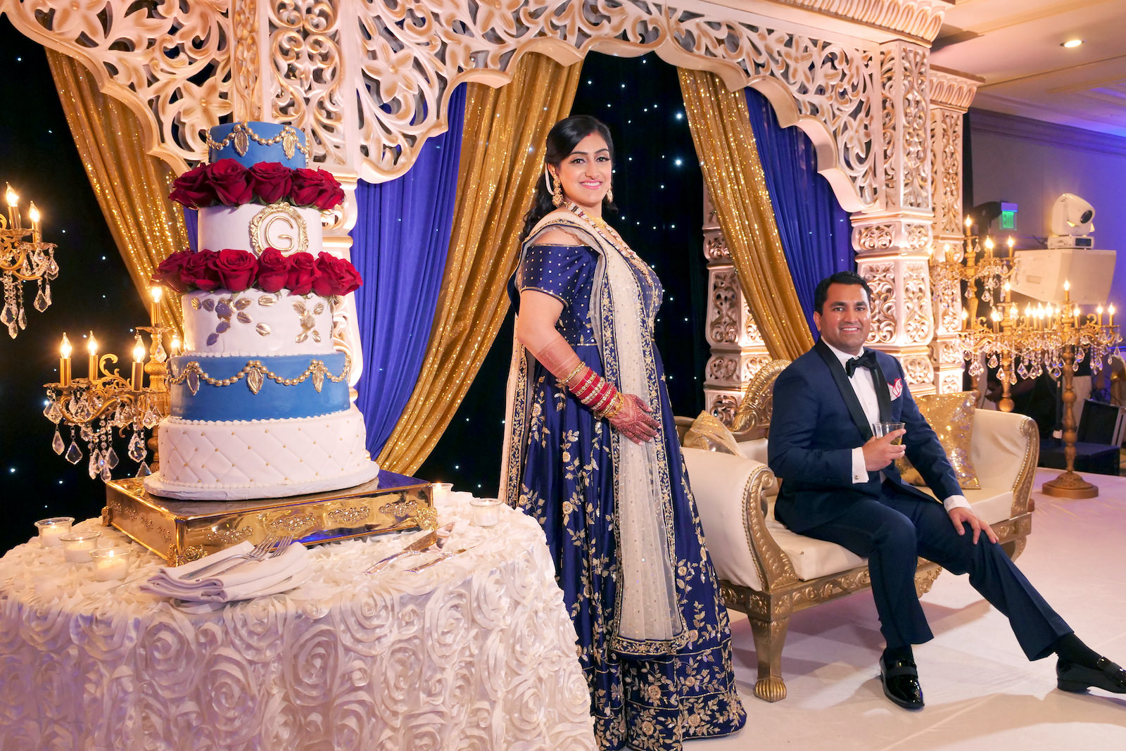Five Tier Fondant Indian Wedding Cake with Gold Monogram and Quilting accented with Red Roses on a Gold Cake Stand | White Gold and Blue Indian Wedding Mandap Stage with Gold Candelabras | Navy Blue and Gold Indian Wedding Dress | Indian Groom in Classic Navy Blue Tuxedo