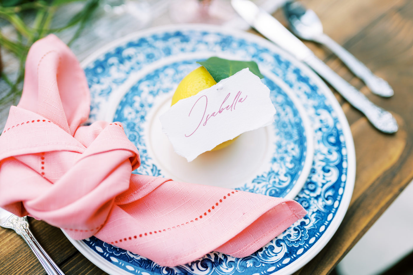 Bright Colorful Florida Citrus Wedding Inspiration | Wedding Place Settings with Vintage Blue China and Pink Hemstitch Knot Napkins and Citrus Lemon Place Cards
