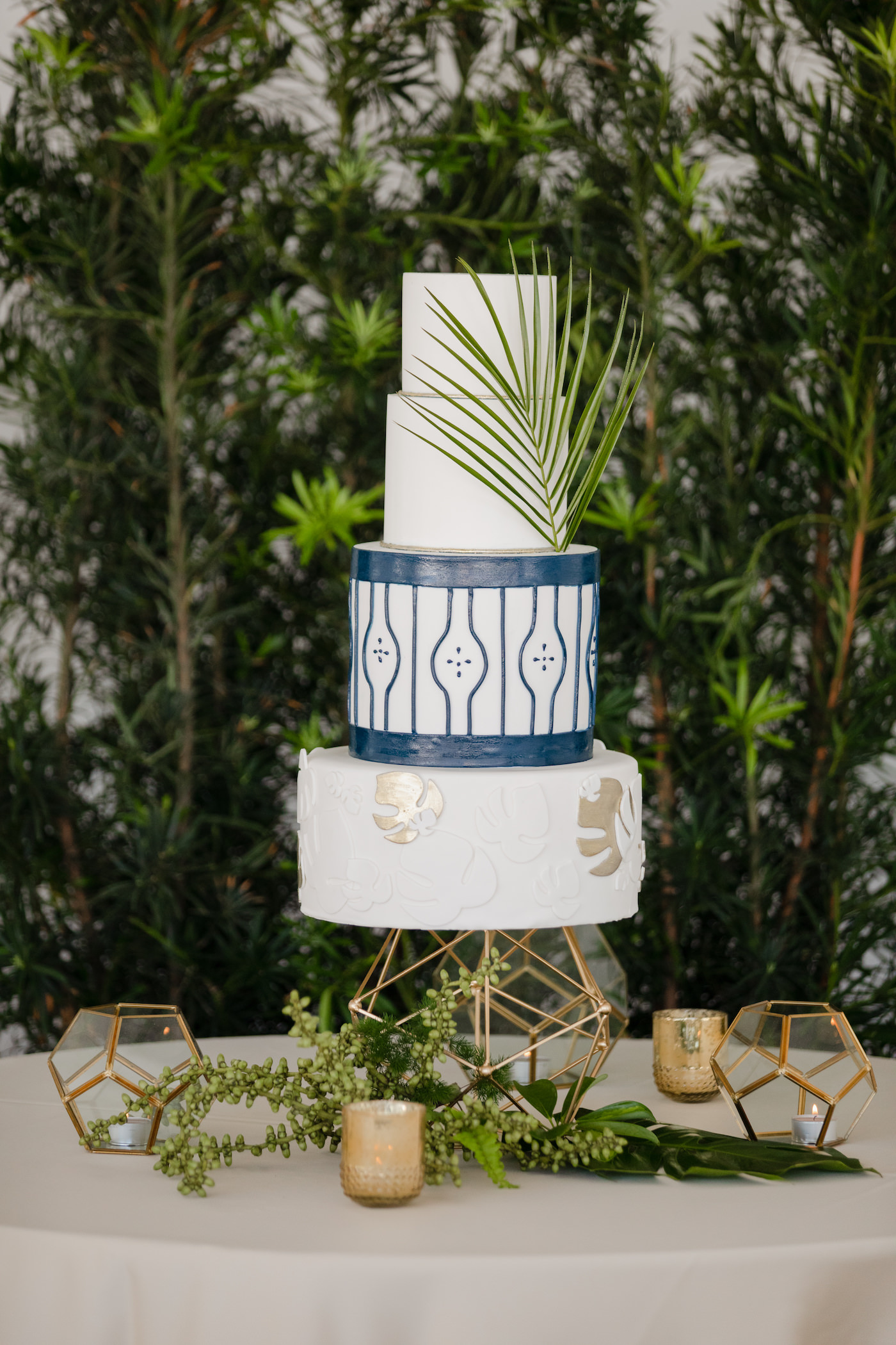 Clearwater Beach Wedding Venue Hilton Clearwater Beach   Modern Tropical Beach Outdoor Wedding Cake Table with Four Tier Gold and Navy Wedding Cake accented with Palm Frond Leaf on Gold Geometric Stand