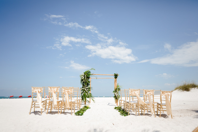 Clearwater Beach Wedding Venue Hilton Clearwater Beach   Modern Tropical Beach Wedding Ceremony with Gold Chiavari Chairs and Champagne Sash Bows and Tropical Palm Frond Leaf Floral Arrangements on Bamboo Arch   Palm Leaves Lining Beach Sand Aisle