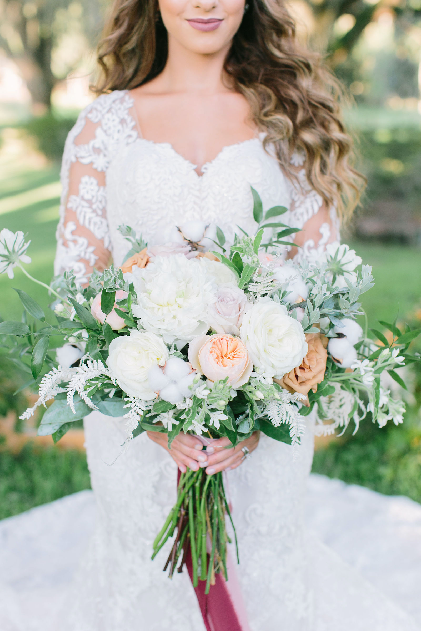 Outdoor Florida Bridal Portrait | Lace Mermaid Long Sleeve Low Back Illusion Lace Bridal Gown Wedding Dress | Ivory Champagne and Peach Natural Bouquet with Roses Peonies Astilbe and Greenery tied with Blush Pink and Mauve Ribbons