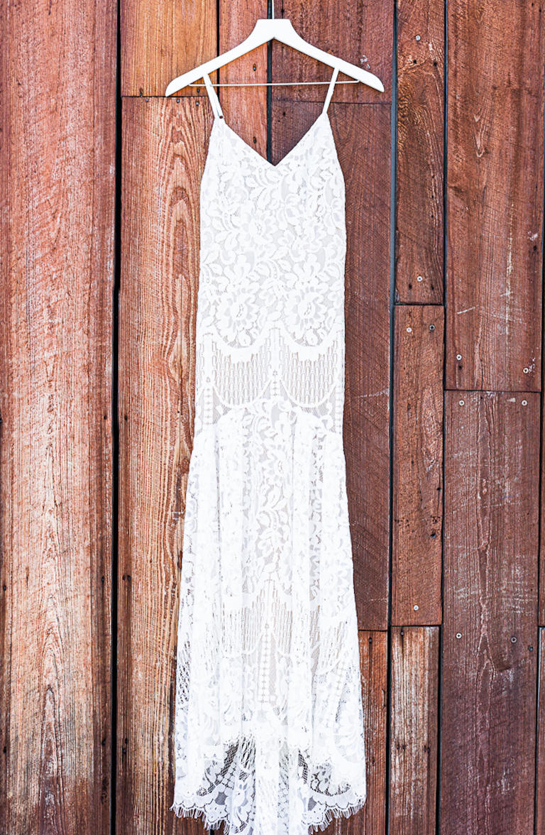 Lace Sheath Spaghetti Strap V Neck Boho Bridal Gown Wedding Dress | Wedding Dress Hanger Shot on Rustic Wood Wall