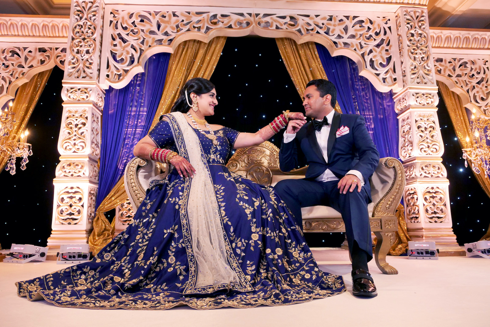 Indian Bride and Groom Wedding Portrait | White Gold and Blue Indian Wedding Mandap Stage with Gold Candelabras | Navy Blue and Gold Indian Wedding Dress | Indian Groom in Classic Navy Blue Tuxedo
