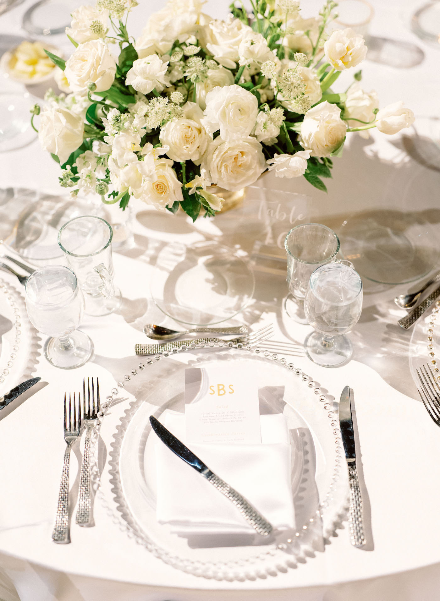 Romantic, Modern Outdoor Florida Wedding Reception Decor, White Linens and Clear Acrylic Stemware and Chargers, Custom Menu, Low Floral Centerpieces with Ivory Roses, White Babies Breath and Greenery | Luxury Sarasota Wedding Planner NK Weddings