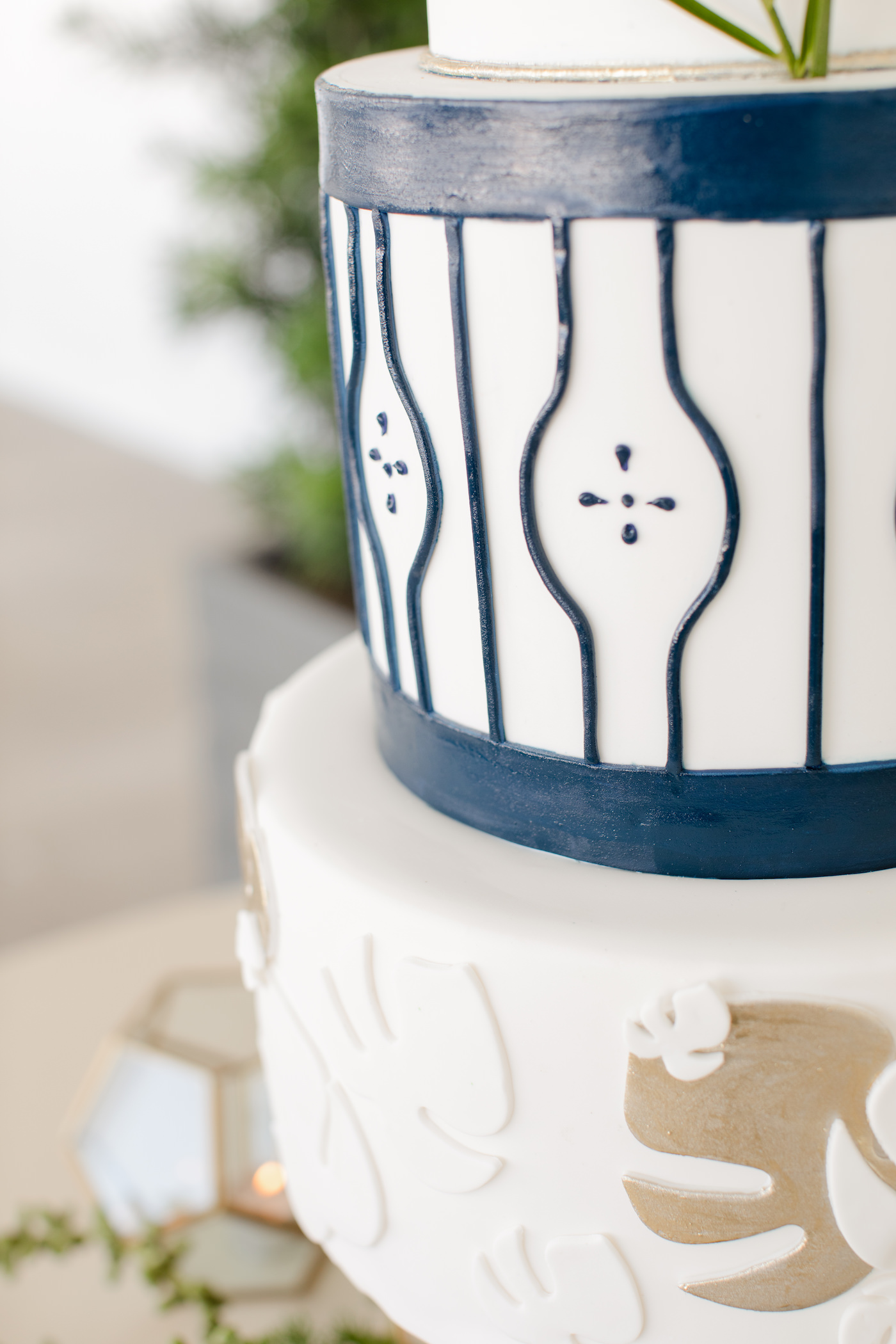 Clearwater Beach Wedding Venue Hilton Clearwater Beach   Modern Tropical Beach Outdoor Wedding Cake Table with Four Tier Gold and Navy Wedding Cake with Monstera Palm Leaf Motif