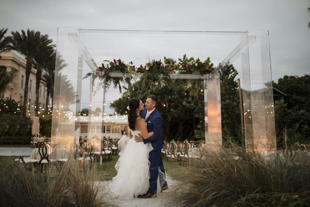 Bride and Groom Outdoor Portrait Sarasota Beach Wedding Ceremony on Siesta Key | Groom in Navy Blue Suit with Blush Pink Neck Tie | Horsehair Trim Tiered Organza Tulle Ballgown Bridal Gown with Sweetheart Neckline and Lace Bodice | Sarasota Wedding Dress Shop Truly Forever Bridal | Acrylic Four Post Arbor Backdrop with White and Deep Red and Blush Pink Floral Arrangement Garland with Eucalyptus Greenery