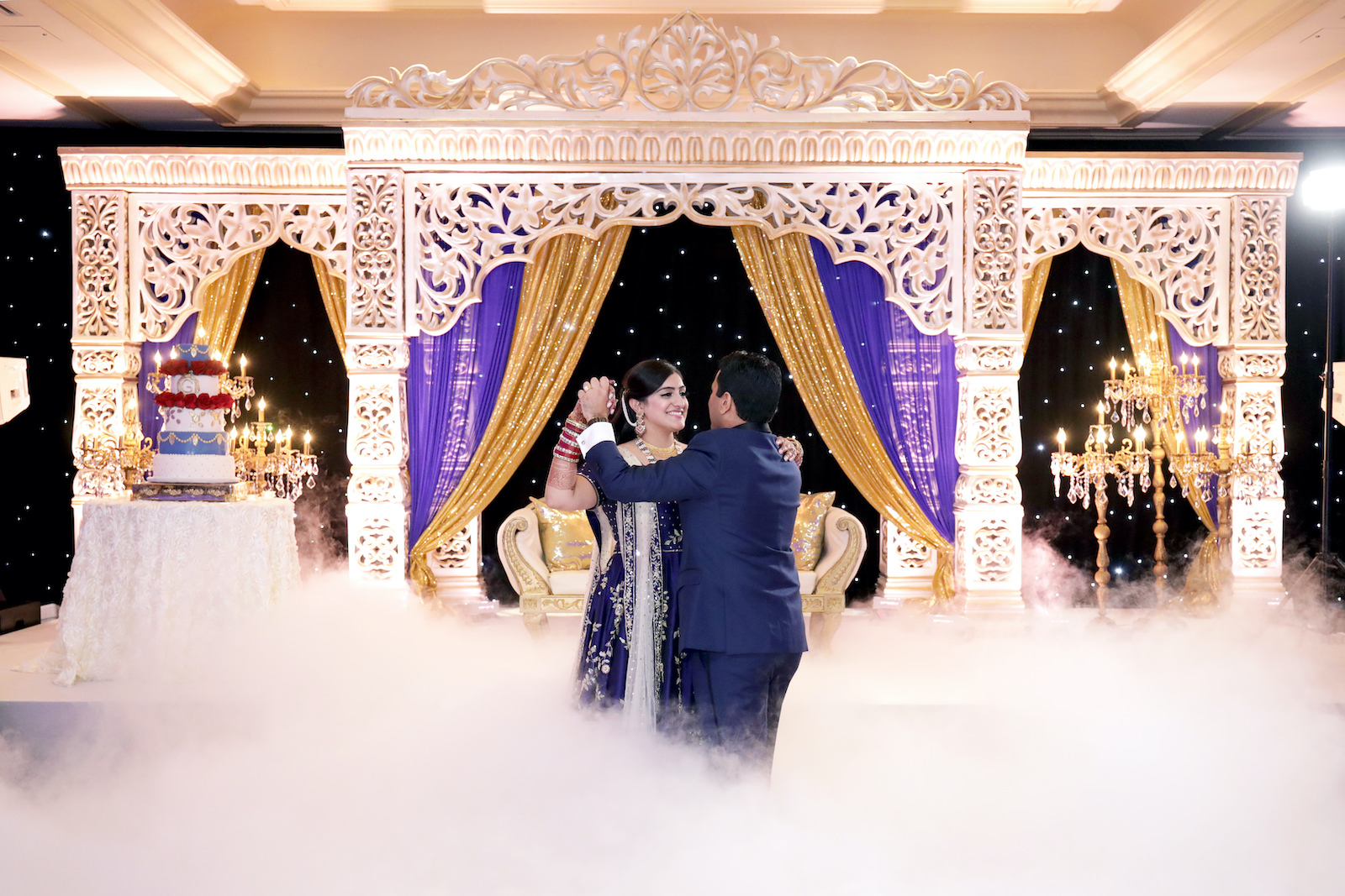 Indian Bride and Groom First Dance with Fog Machine| White Gold and Blue Indian Wedding Mandap Stage with Gold Candelabras | Navy Blue and Gold Indian Wedding Dress | Indian Groom in Classic Navy Blue Tuxedo