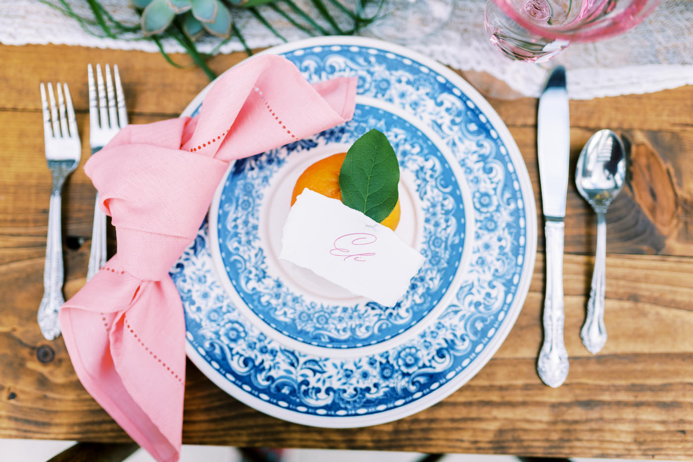 Bright Colorful Florida Citrus Wedding Inspiration | Wedding Place Settings with Vintage Blue China and Pink Hemstitch Knot Napkins and Citrus Orange Place Cards