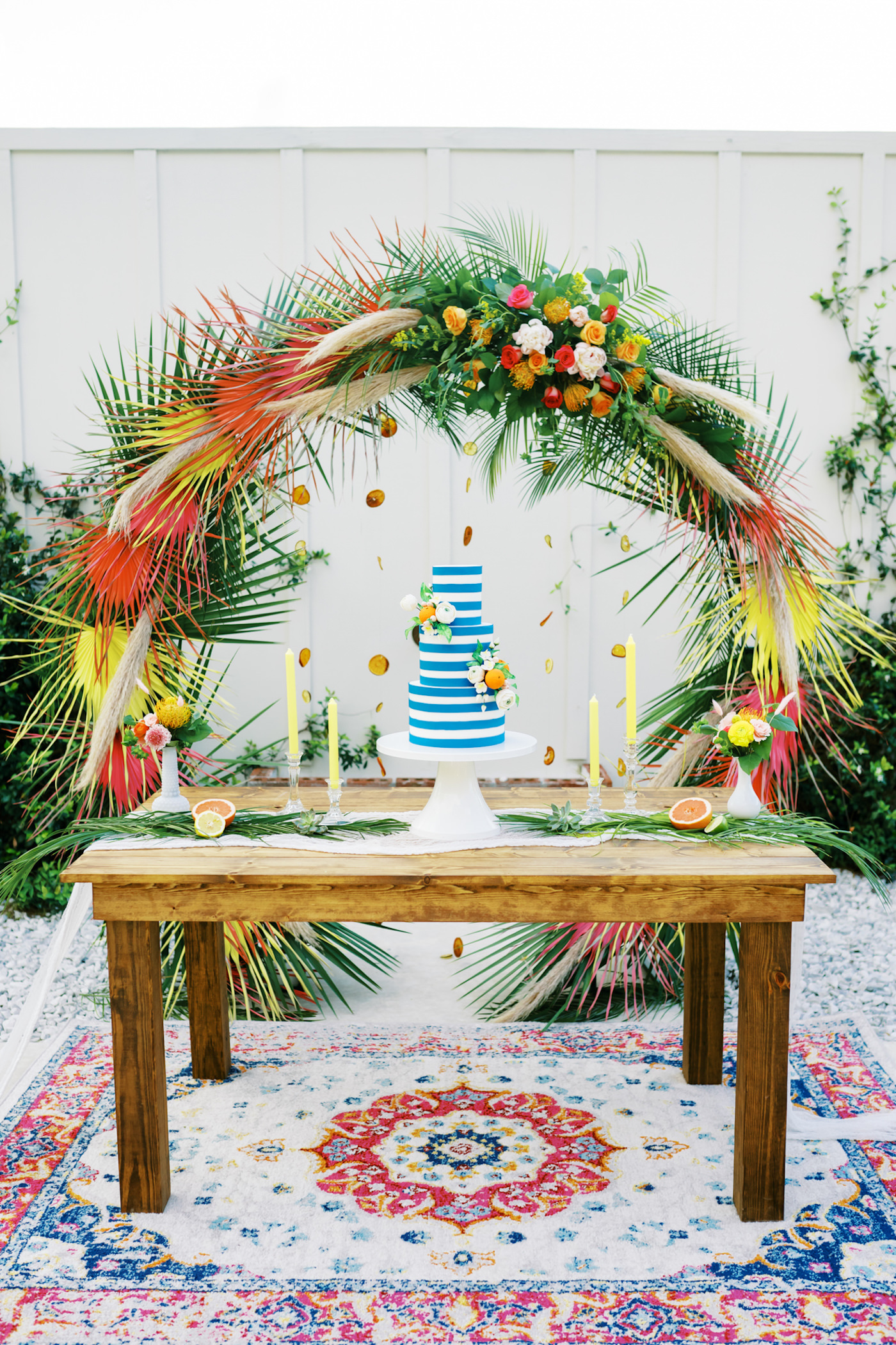 Wood Farm Table Wedding Cake Display | Three Tier Blue and White Stripe Wedding Cake with Fresh Citrus by Tampa Bay Cake Company Bakery | Tropical Florida Citrus Wedding Inspiration | Orange and Yellow Painted Palm Frond Leaf Round Moon Arch Ceremony Backdrop with Pampas Grass and Hanging Orange Slices | Bright Colorful Floral Arrangement with Orange and Pink Roses and Yellow Pincushion Protea