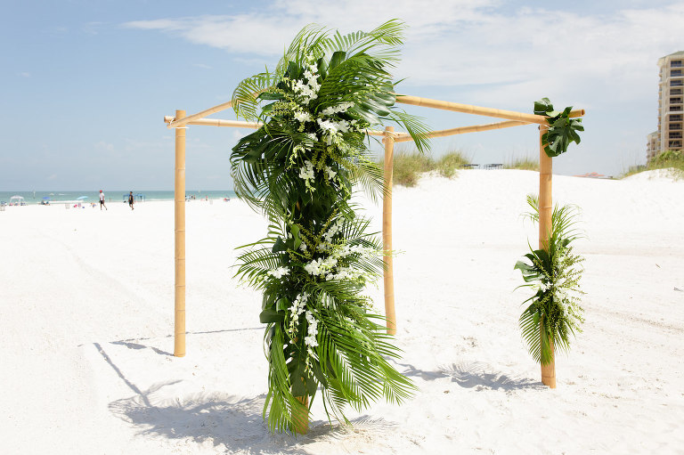 Clearwater Beach Wedding Venue Hilton Clearwater Beach | Modern Tropical Beach Wedding Ceremony with Tropical Palm Frond Leaf and Orchid Floral Arrangements on Bamboo Arch