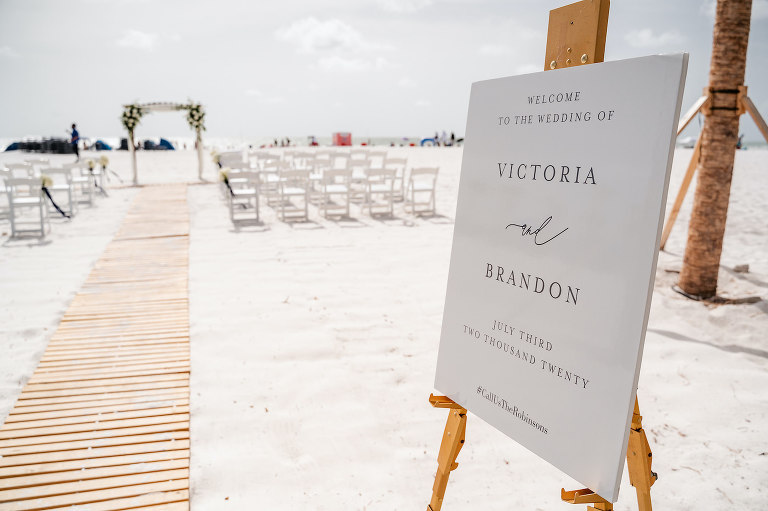 Tampa Bay Beach Wedding Ceremony, Outdoor Beachfront Ceremony on the White Powder Sand with Tropical Decor, Elegant Black Script Welcome Sign Victoria and Brandon, Bamboo Wooden Aisle Runner | Florida Hotel and Wedding Venue Hilton Clearwater Beach