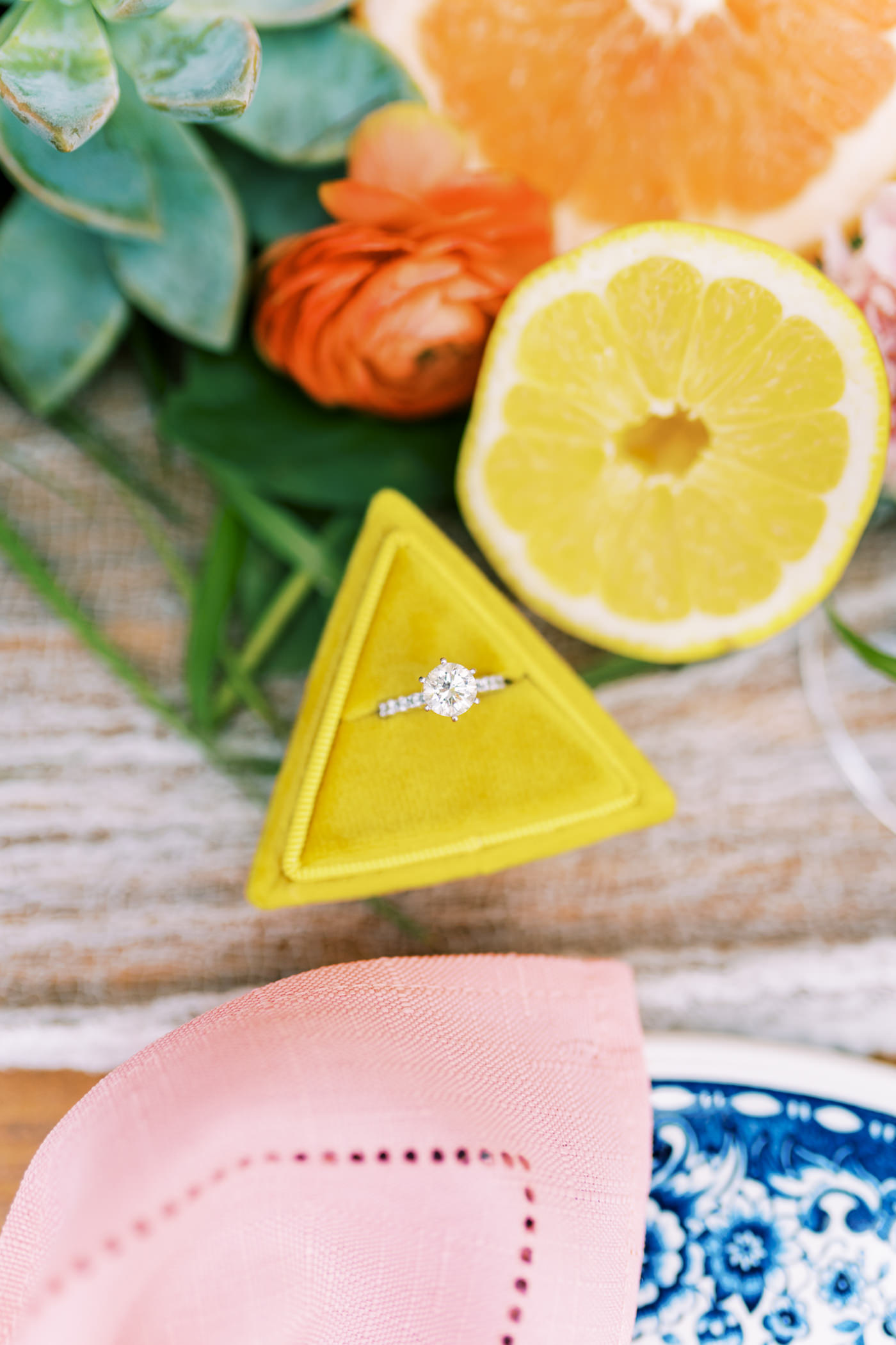 Florida Citrus Wedding Inspiration with Yellow Velvet Ring Box | Wedding Ring Shot with Round Solitaire Diamond Engagement Ring with Channel Set Diamonds Band