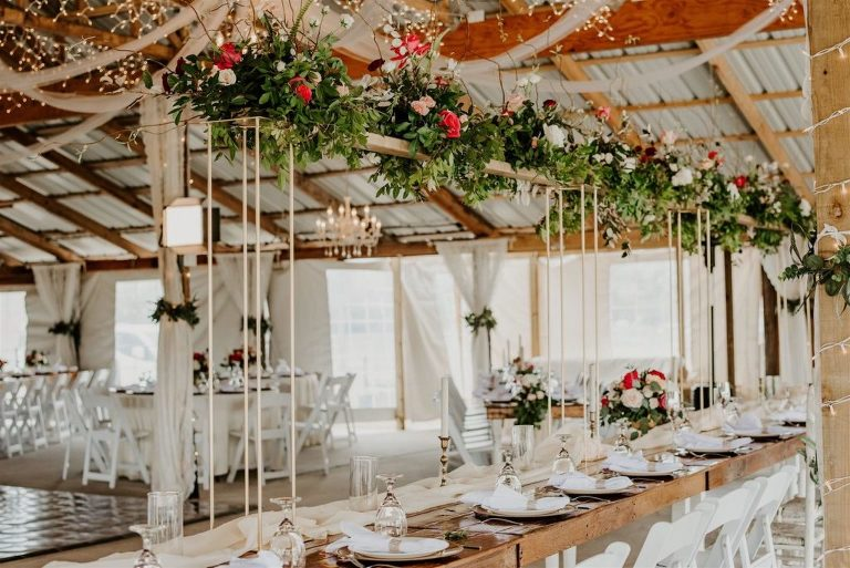 Rustic Barn Tampa Wedding with Suspended Ceiling Floral Arrangements with Blush Pink and Deep Red Burgundy Roses and Greenery | Wood Farm Tables with Champagne Linen Runners and Taper Candlestick Candles | Tampa Wedding Florist Monarch Events and Designs