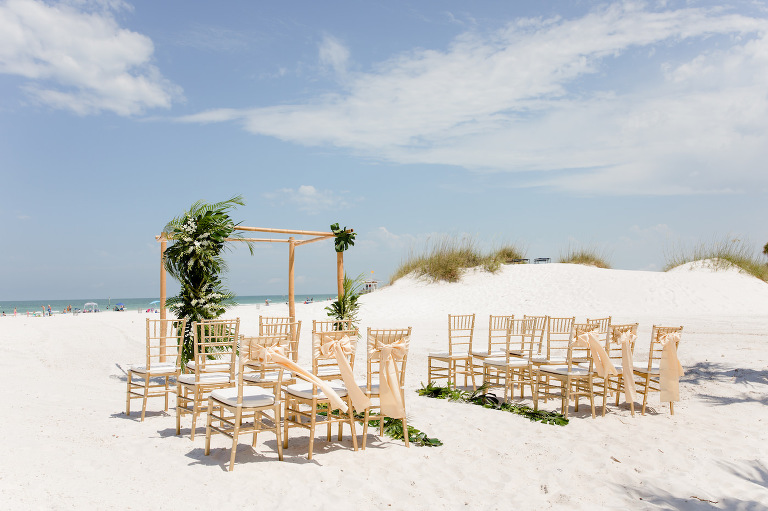 Clearwater Beach Wedding Venue Hilton Clearwater Beach | Modern Tropical Beach Wedding Ceremony with Gold Chiavari Chairs and Champagne Sash Bows and Tropical Palm Frond Leaf Floral Arrangements on Bamboo Arch | Palm Leaves Lining Beach Sand Aisle
